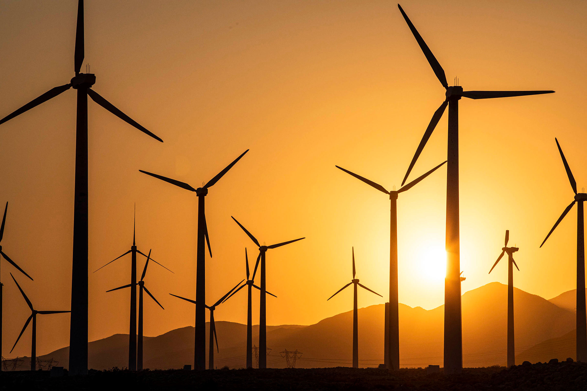 Several wind turbines stand against an orange sky. A bright yellow sun hangs low over mountains in the background.