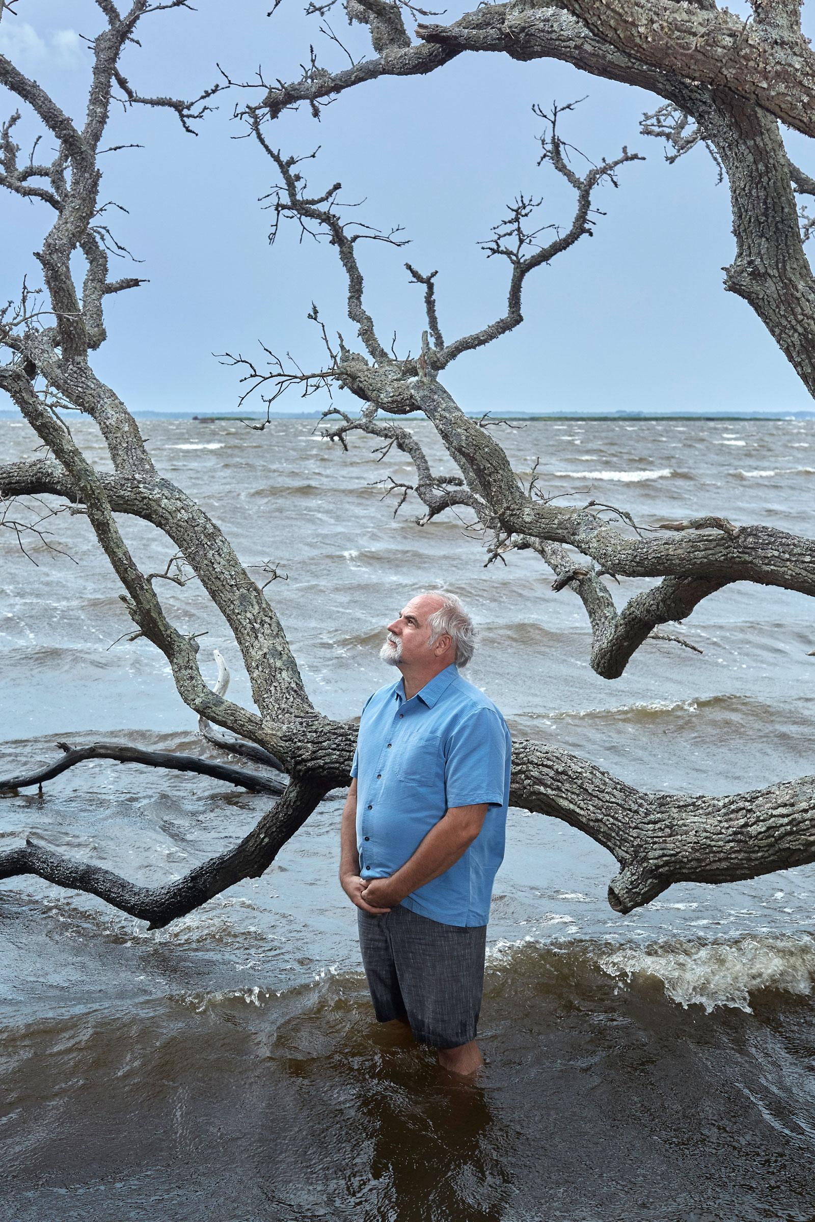 Robbie Fearn, director del centro de Pine Island, de pie junto a un roble que falleció debido a la intrusión de mareas crecientes de agua salada.