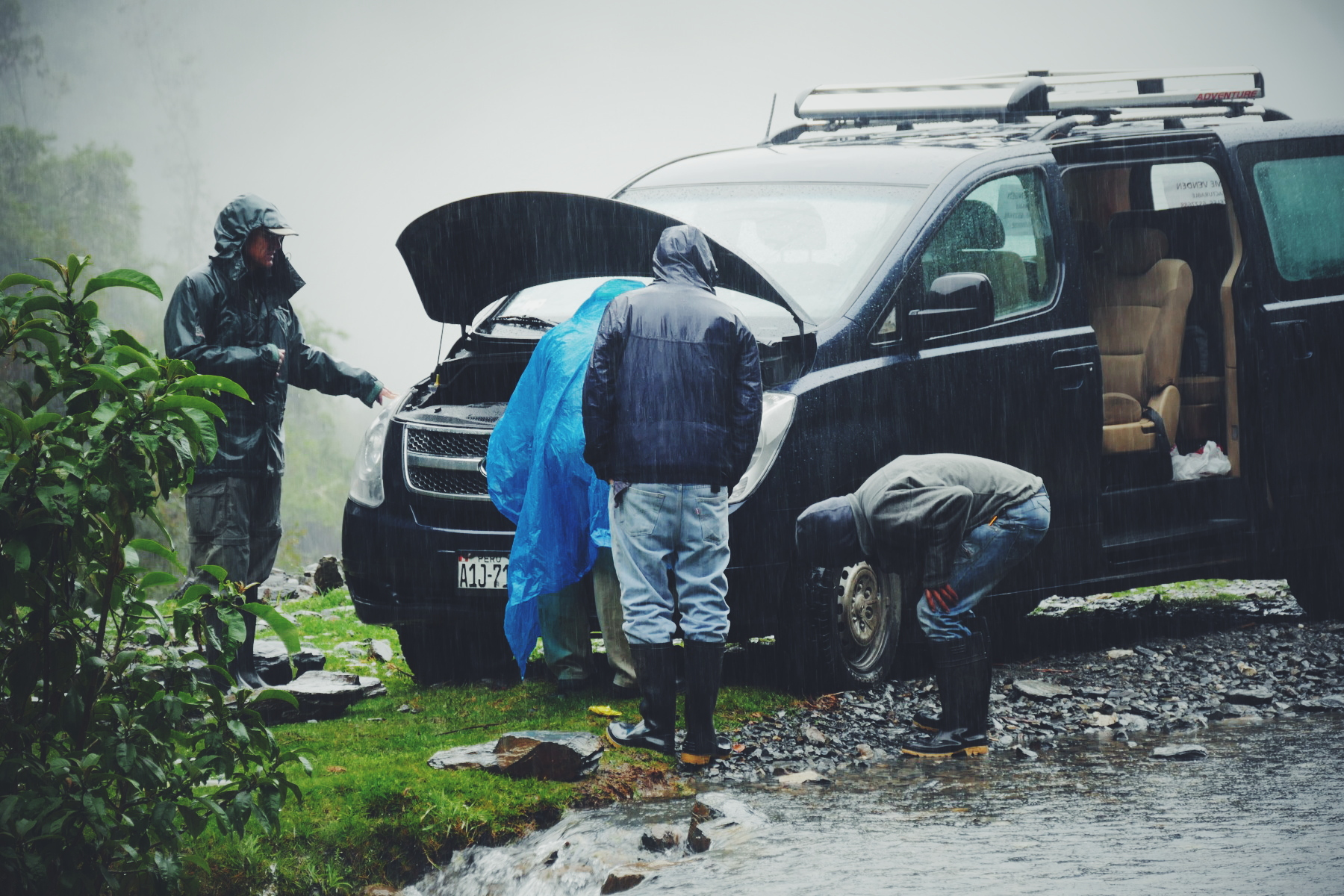 Changing the van's dead battery in a cold drizzle. Noah Strycker