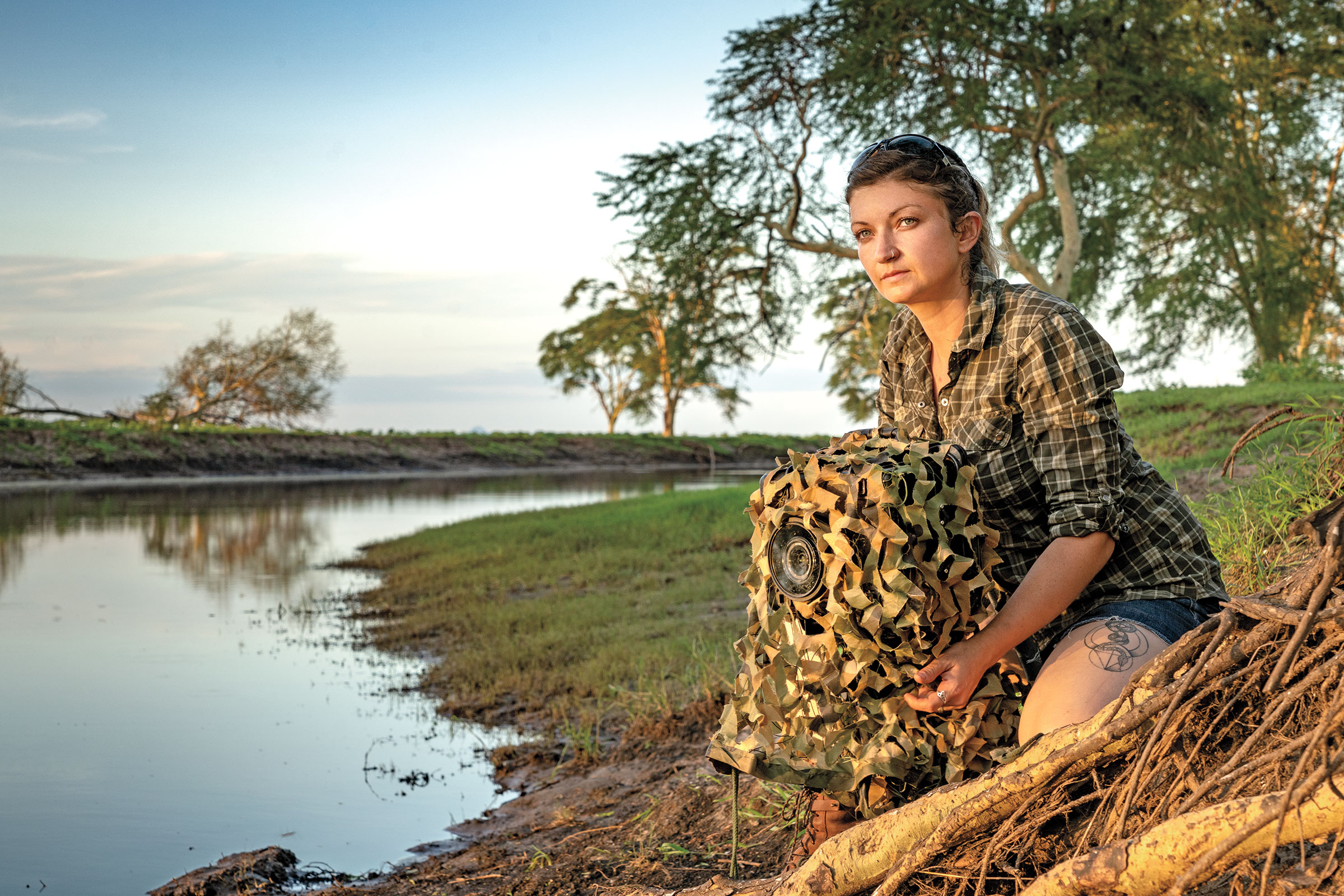 Jen Guyton sets a camera trap at a river in Gorongosa National Park, Mozambique. The trees alongside are a popular nighttime roost and wading birds fish the shallows. Piotr Naskrecki