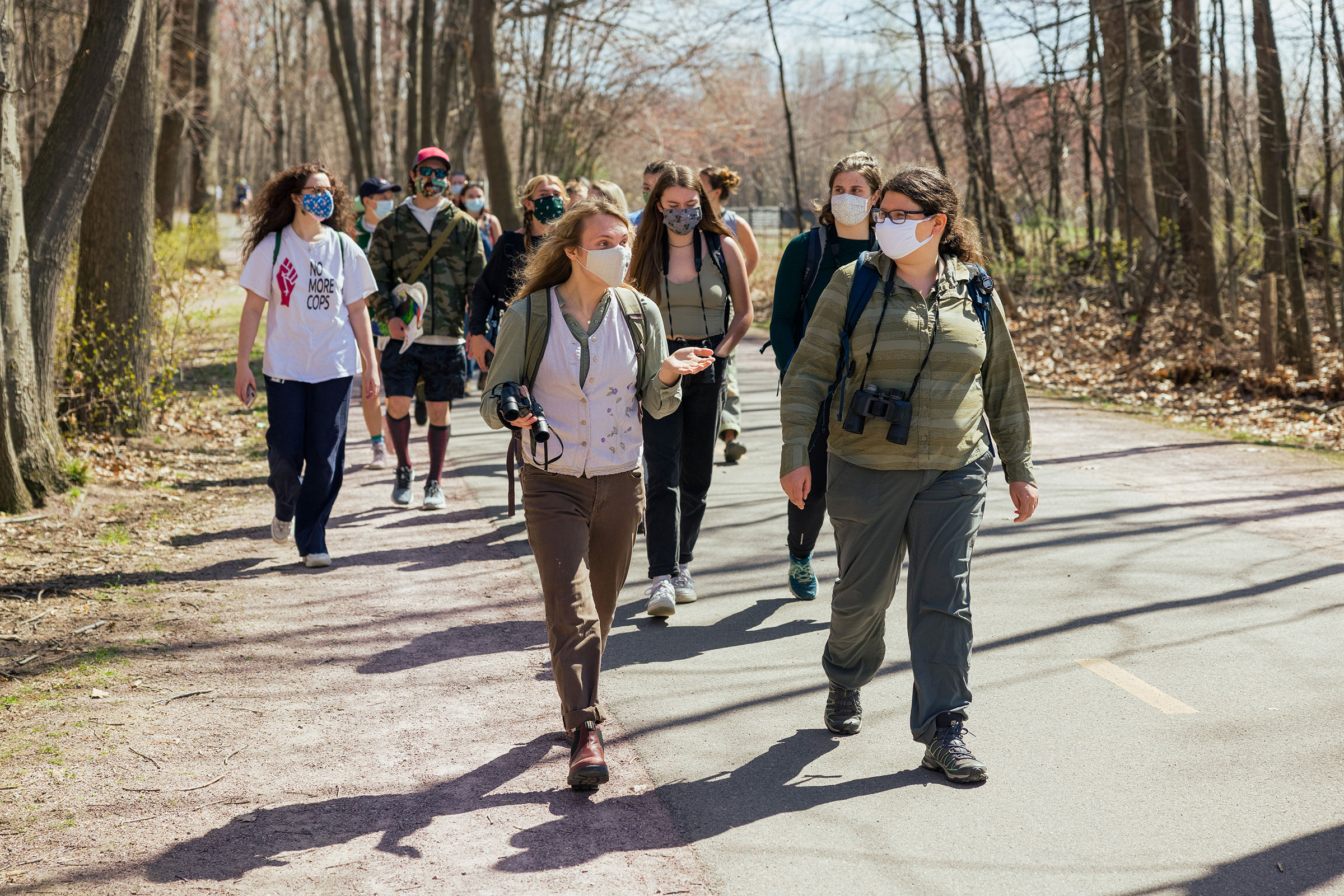 Around one dozen University of Vermont college students wearing face masks and binoculars around their necks walk down a road lined with brown trees during an outdoor class in Spring 2021.