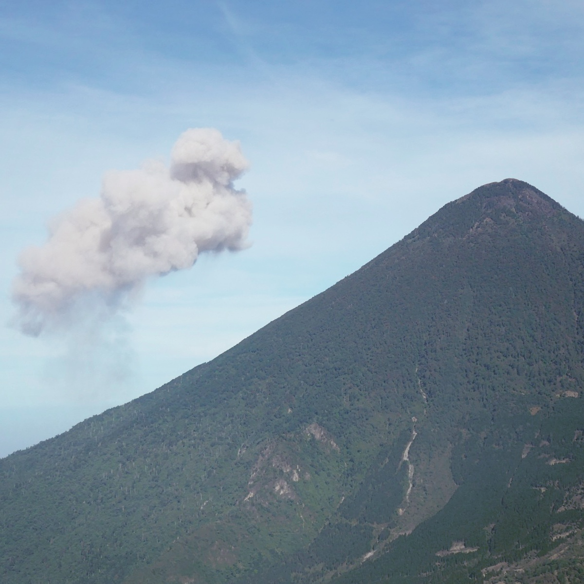 A cloud of ash and steam rises from Guatemala's Santiaguito volcano (hidden behind the cone-shaped Santa Maria volcano in front). Noah Strycker