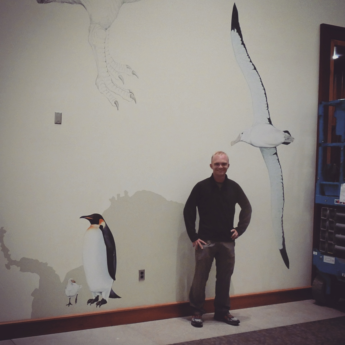 Noah admires a mural in progress at the Cornell Lab of Ornithology. Noah Strycker