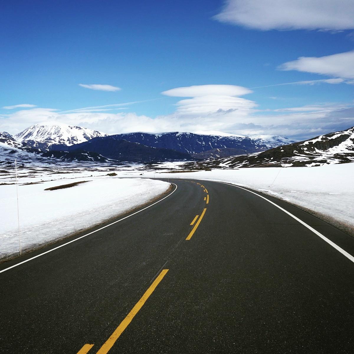 A mountain pass road cuts through the snowpack. Noah Stycker