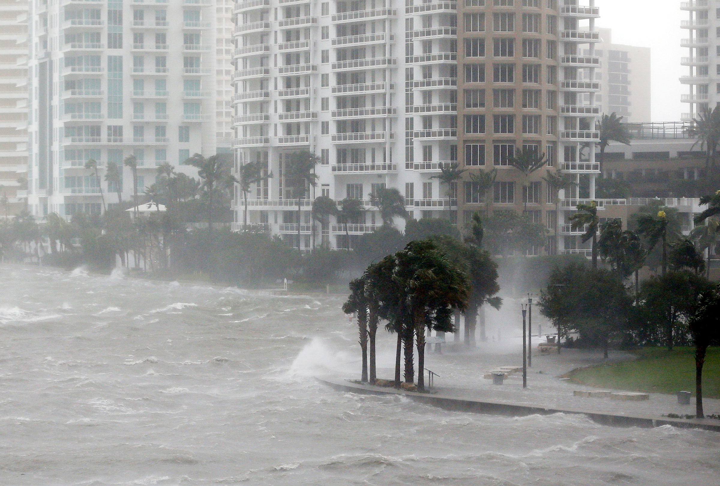 Waves crash over a seawall at the mouth of the Miami River from Biscayne Bay, FL, as Hurricane Irma passed through Miami in September 2017. Stronger hurricanes are one impact of rising global temperatures. Wilfredo Lee/AP