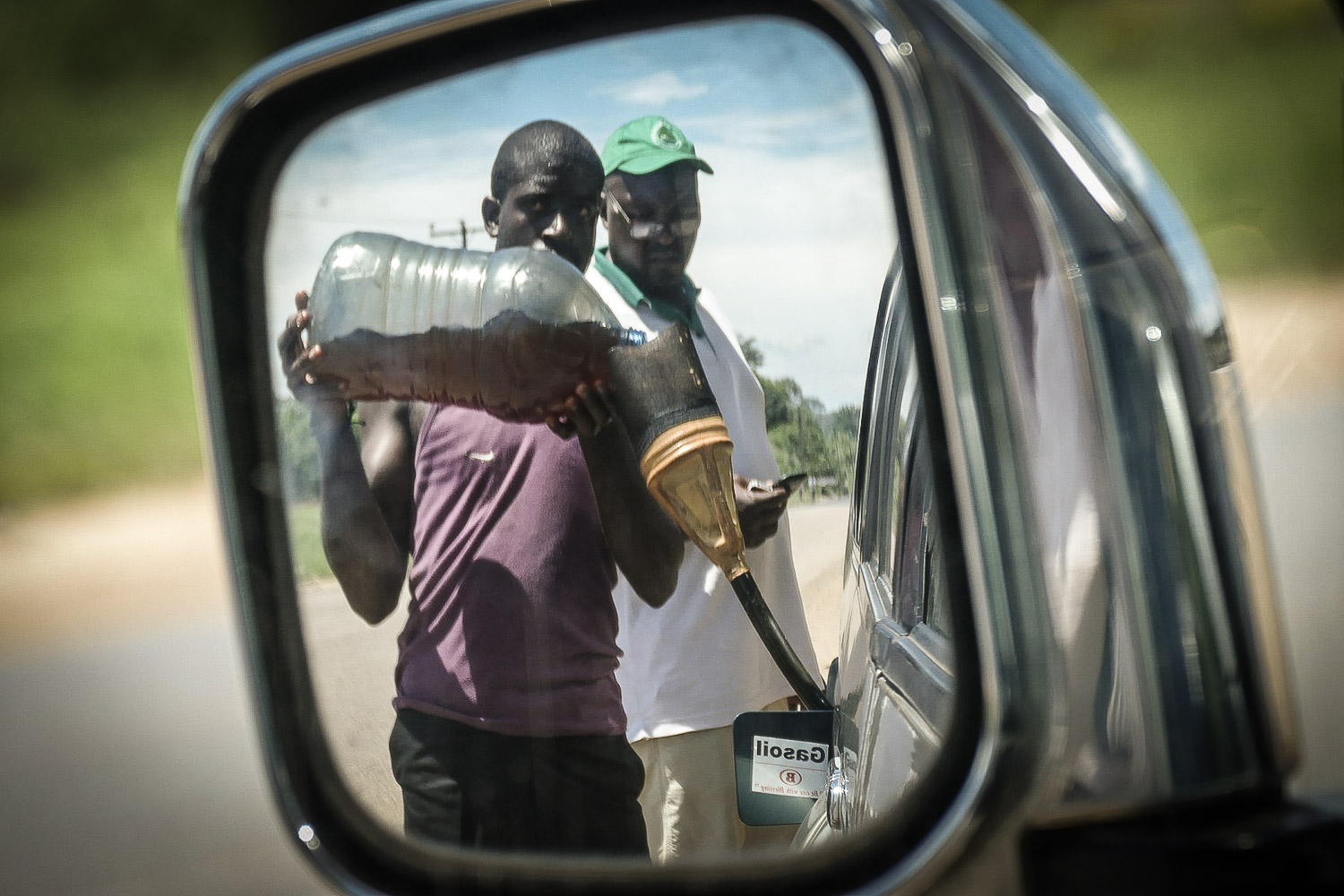 """In Cameroon, sometimes the local filling station is a guy with jugs of """"gasoil"""" and a funnel. Noah Strycker"""