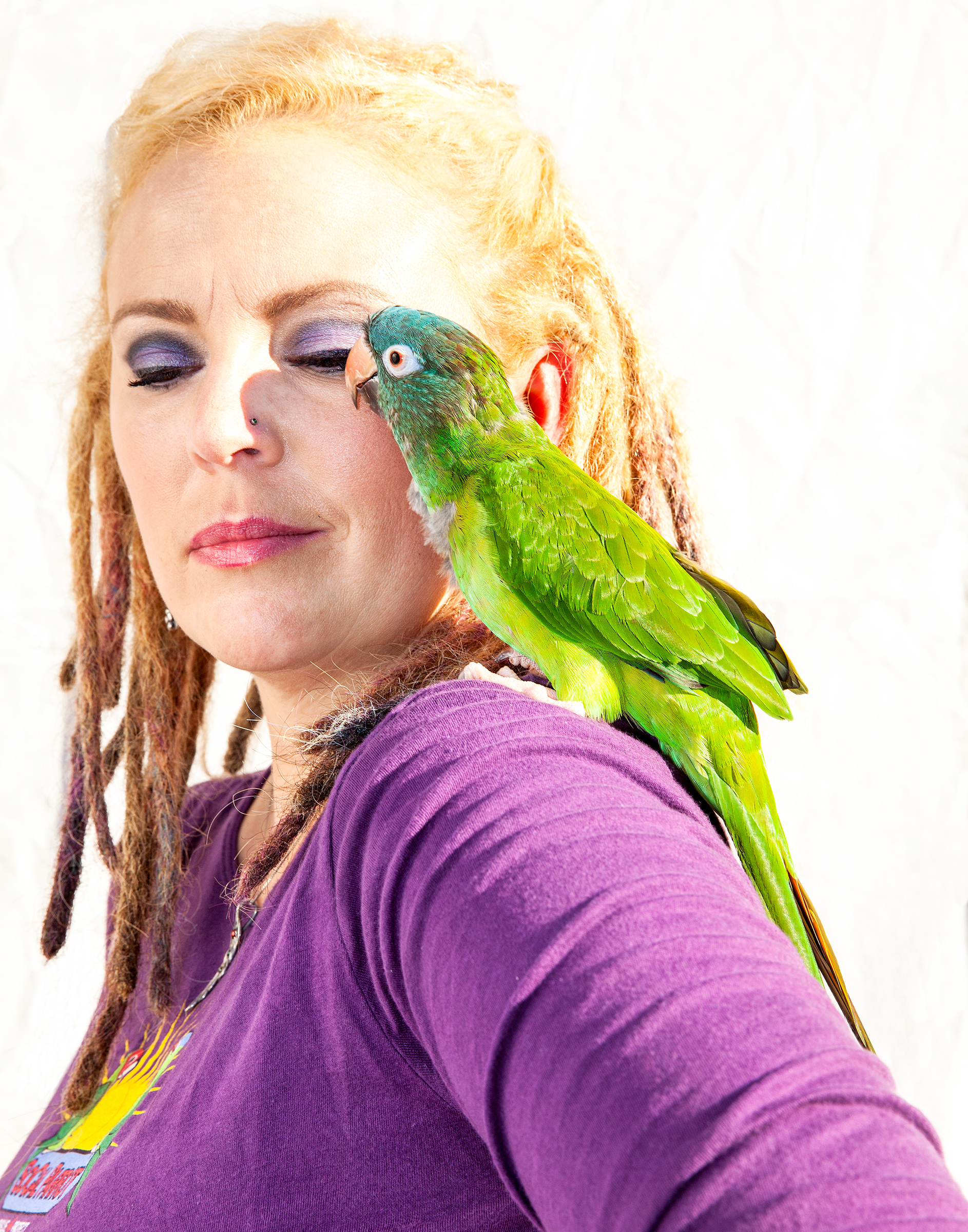 Since 2007 Durham (with a Blue-crowned Parakeet) has opened her home to parrots suffering from various injuries, including electrocution, pellet-gun wounds, and broken wings. Tom Fowlks