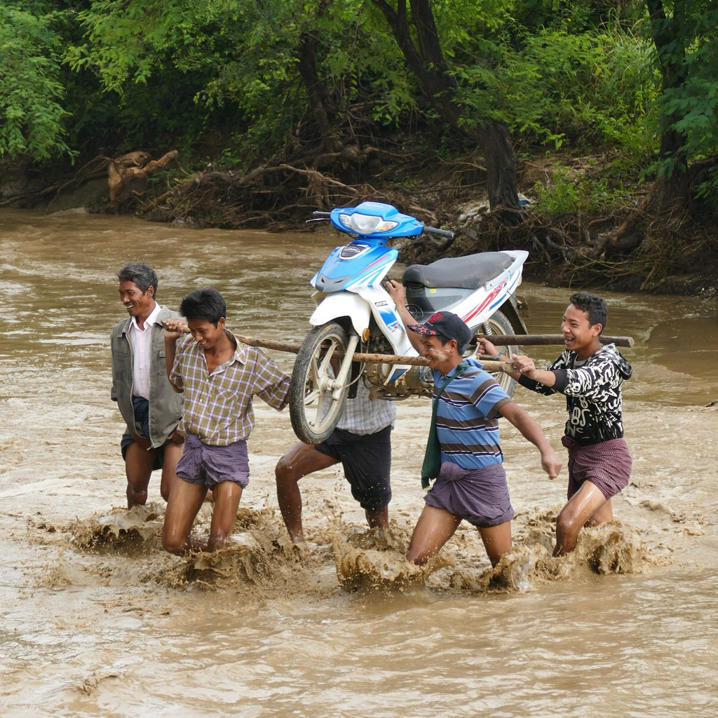 Locals carry a motorcycle across a shallow river ford. Noah Strycker