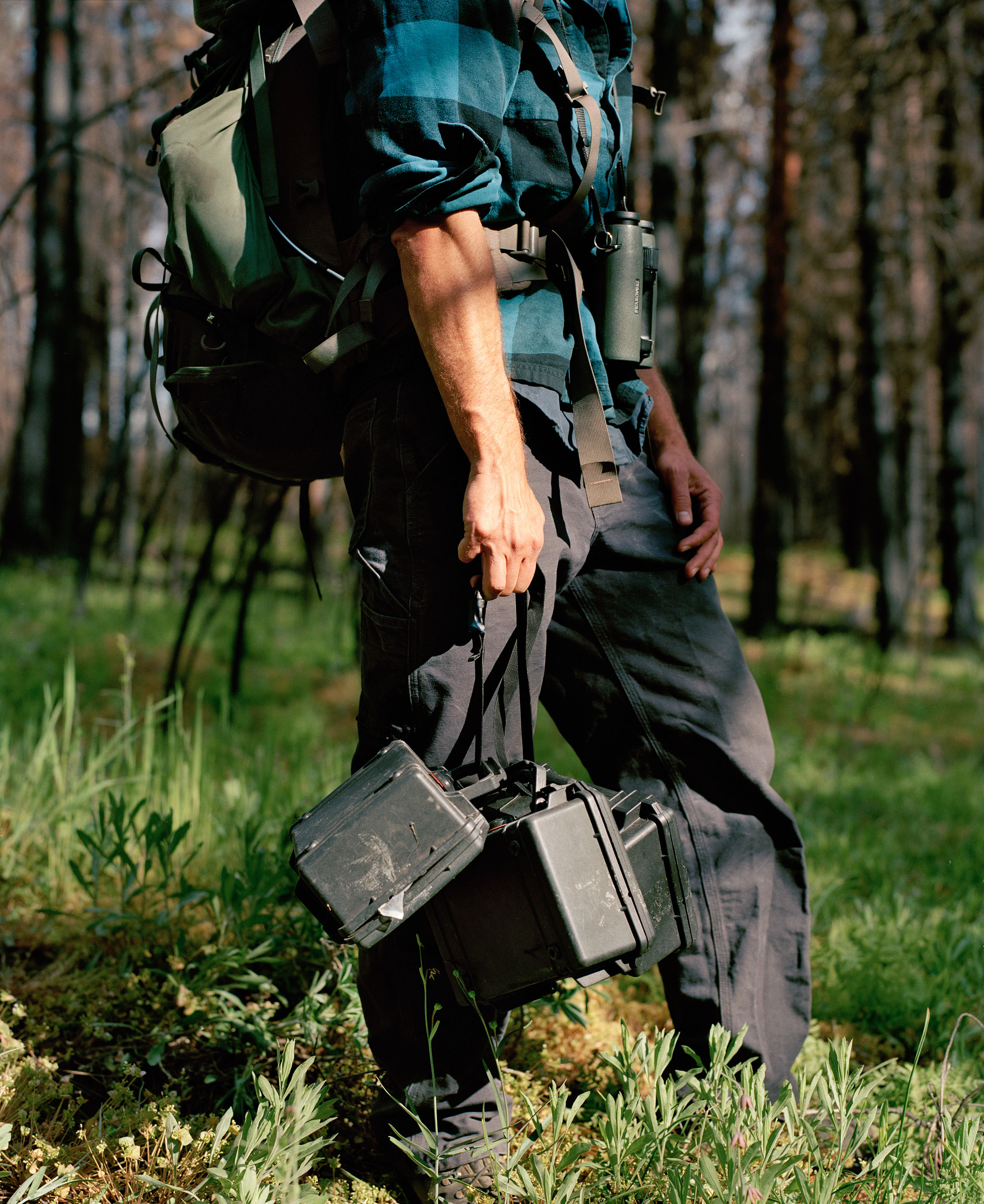 Joe Medley carries recording equipment to set up in a meadow. Jake Stangel