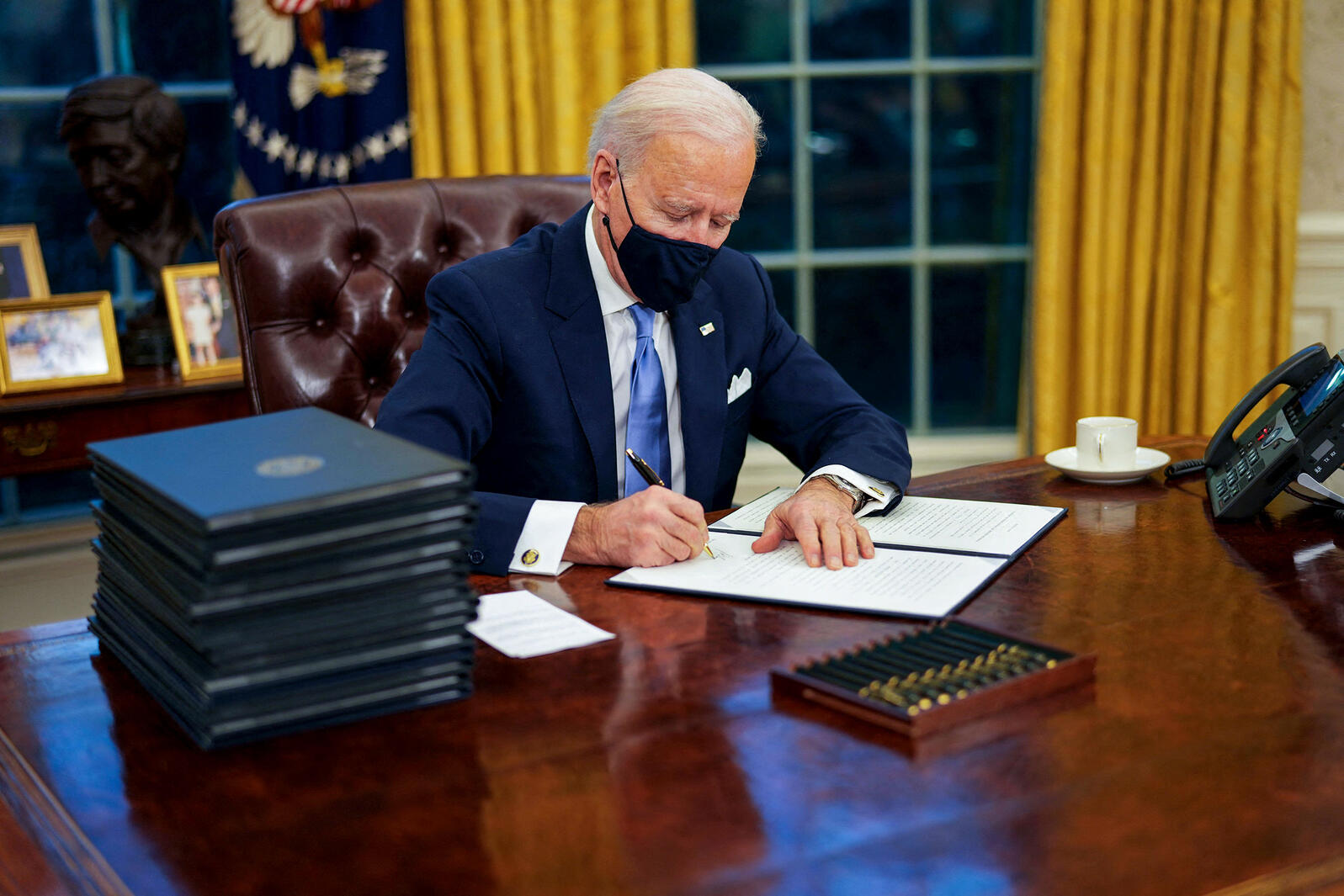 President Joe Biden signs executive orders during his first minutes in the Oval Office, January 20th, 2021. Doug Mills/The New York Times/Alamy