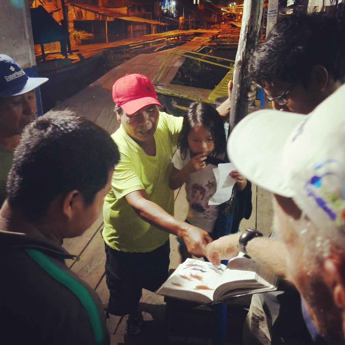 Locals check out a bird book in Iquitos, Peru. Noah Strycker