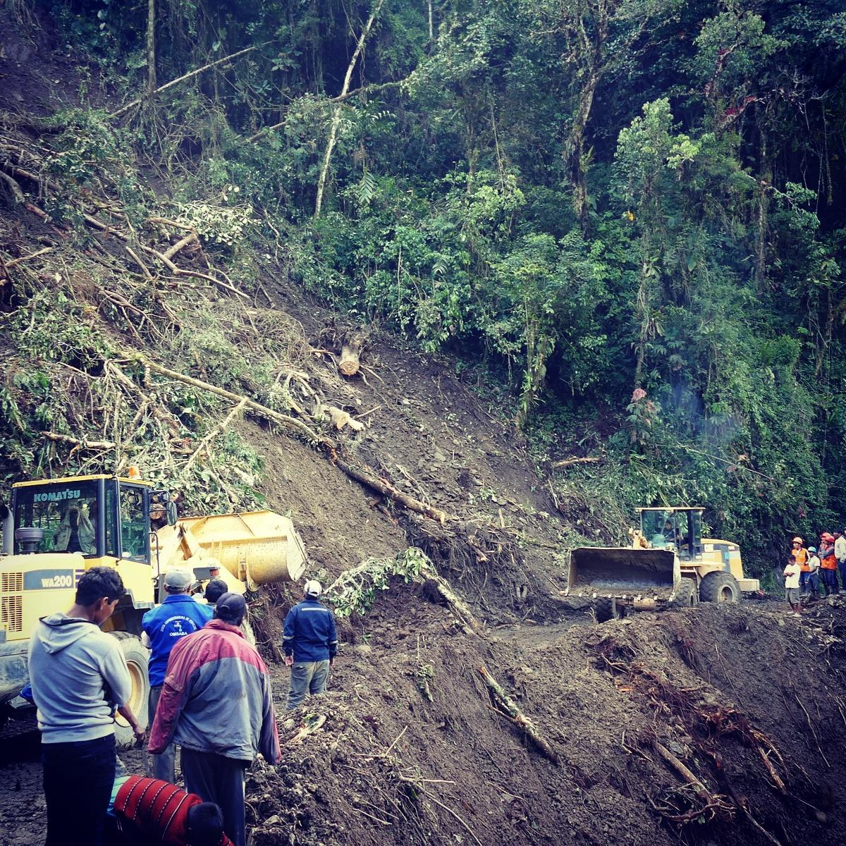 Bulldozers madly clear a landslide on Manu Road while onlookers watch, Peru. Noah Strycker