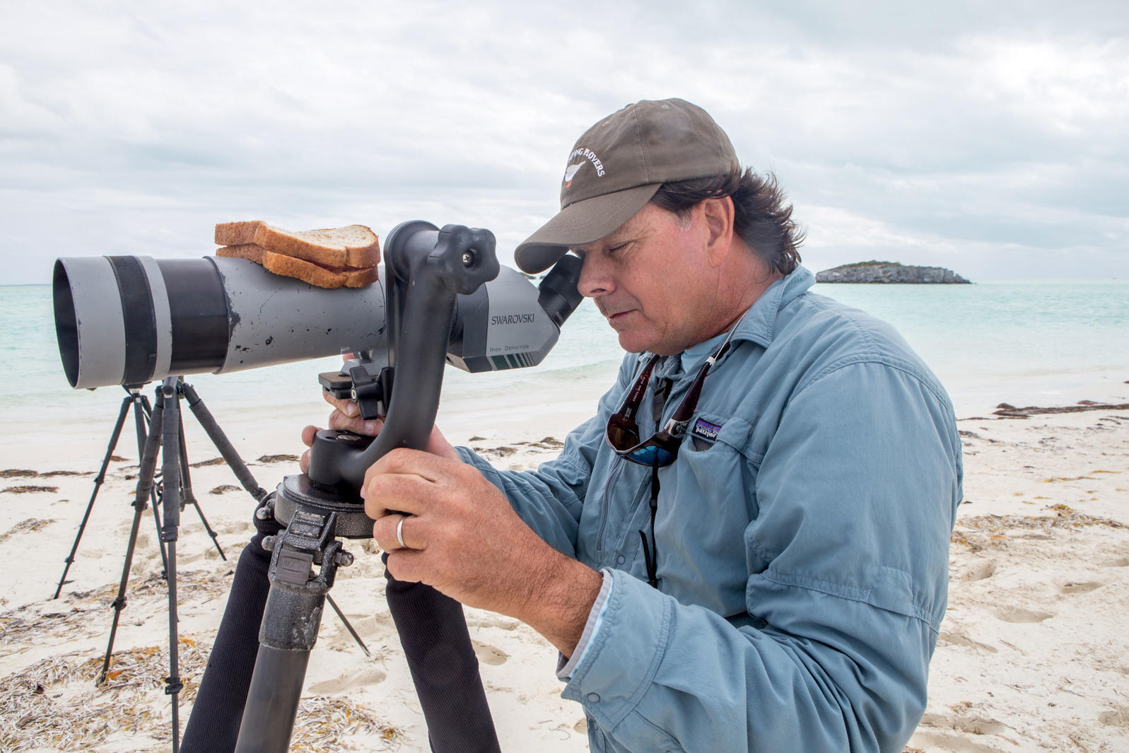 Walker Golder, Audubon Director of the Atlantic Flyway, uses a spotting scope as a plate for his PB&J during the international Piping Plover survey in the Bahamas. Camilla Cerea/Audubon