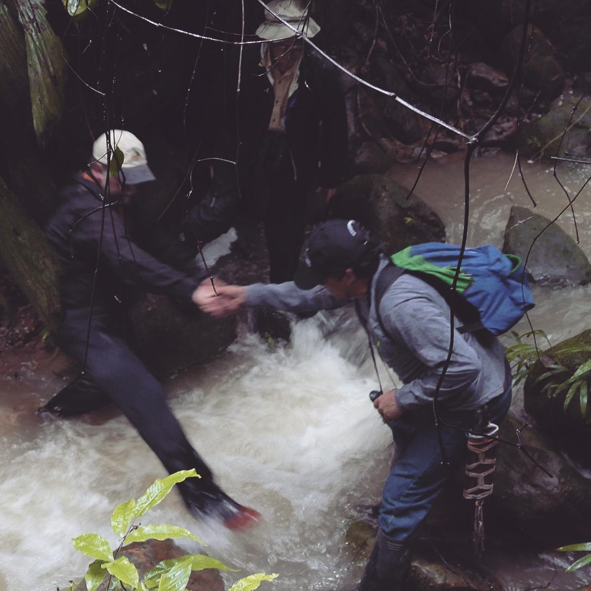 Arturo helps Jim cross a stream while Bruce supervises, Colombia. Noah Strycker