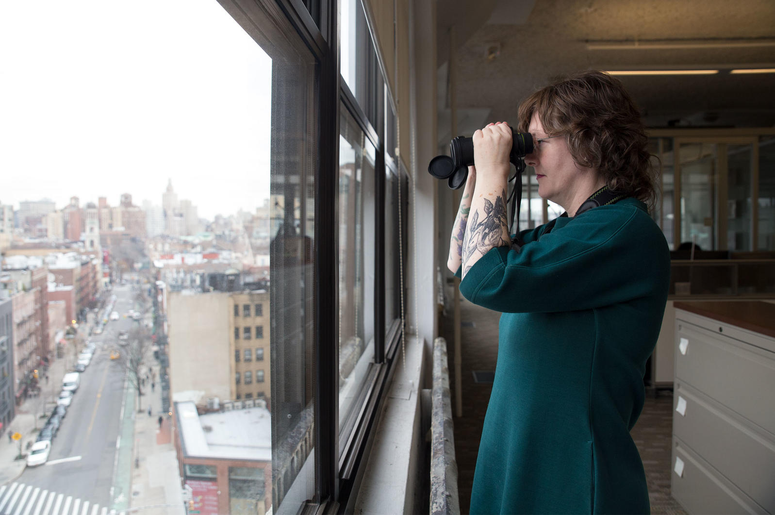 Martha Harbison, network content editor for the National Audubon Society, scans for birds from the windows of Audubon's New York City headquarters. Lia Bocchiaro/Audubon