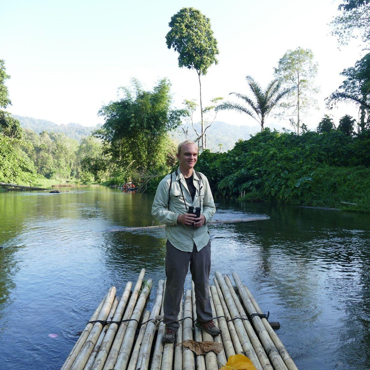 Noah balances on a bamboo raft to reach the forest. Noah Strycker