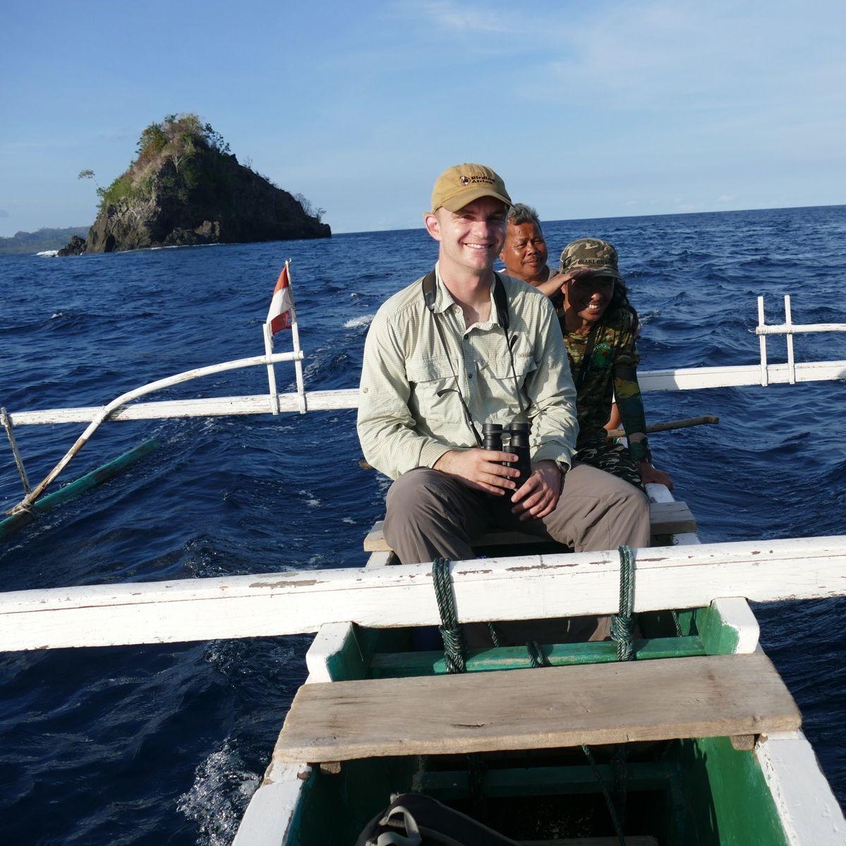 Noah rides an outrigger canoe off Tangkoko. Noah Strycker