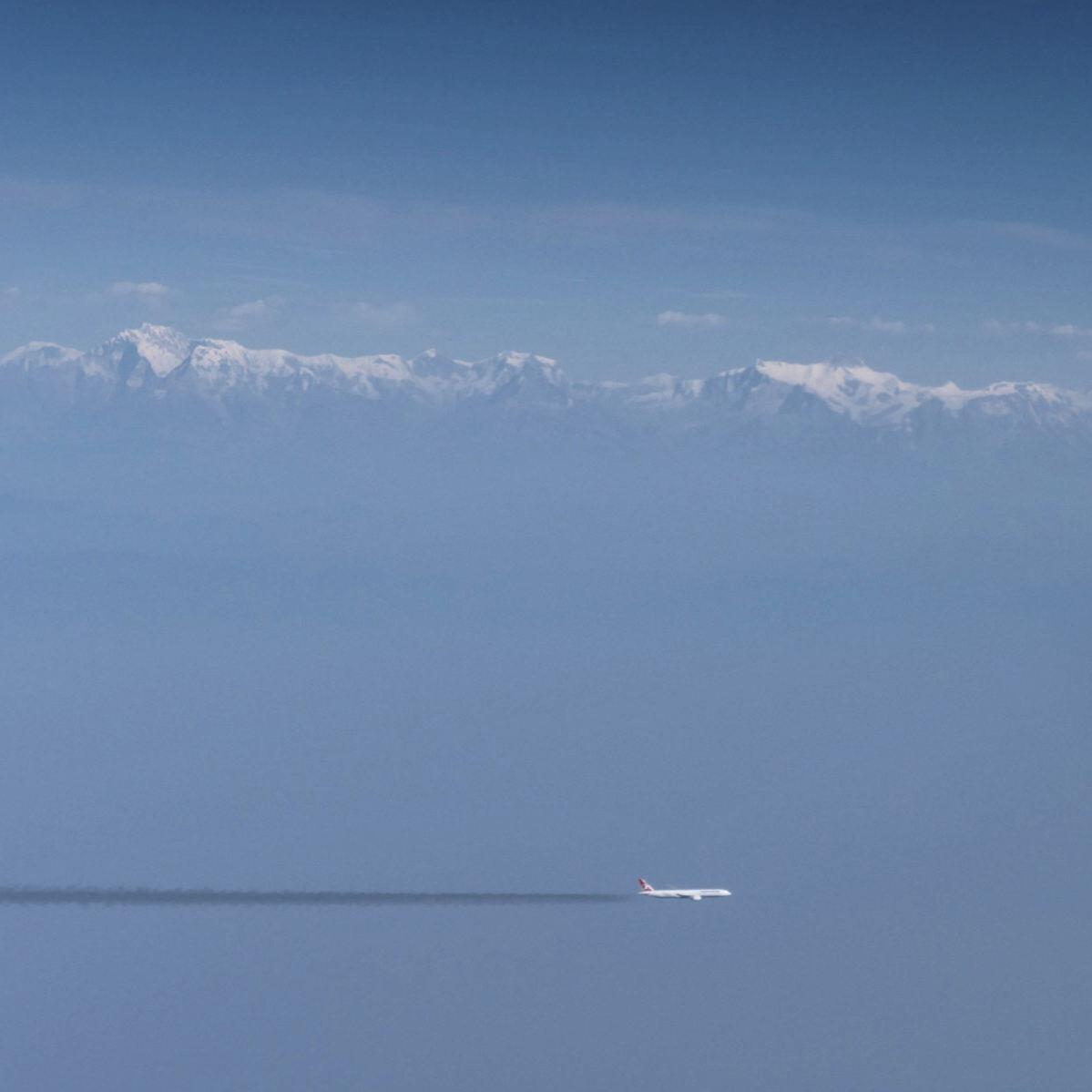 An airplane flies in front of the Himalaya range. Noah Strycker