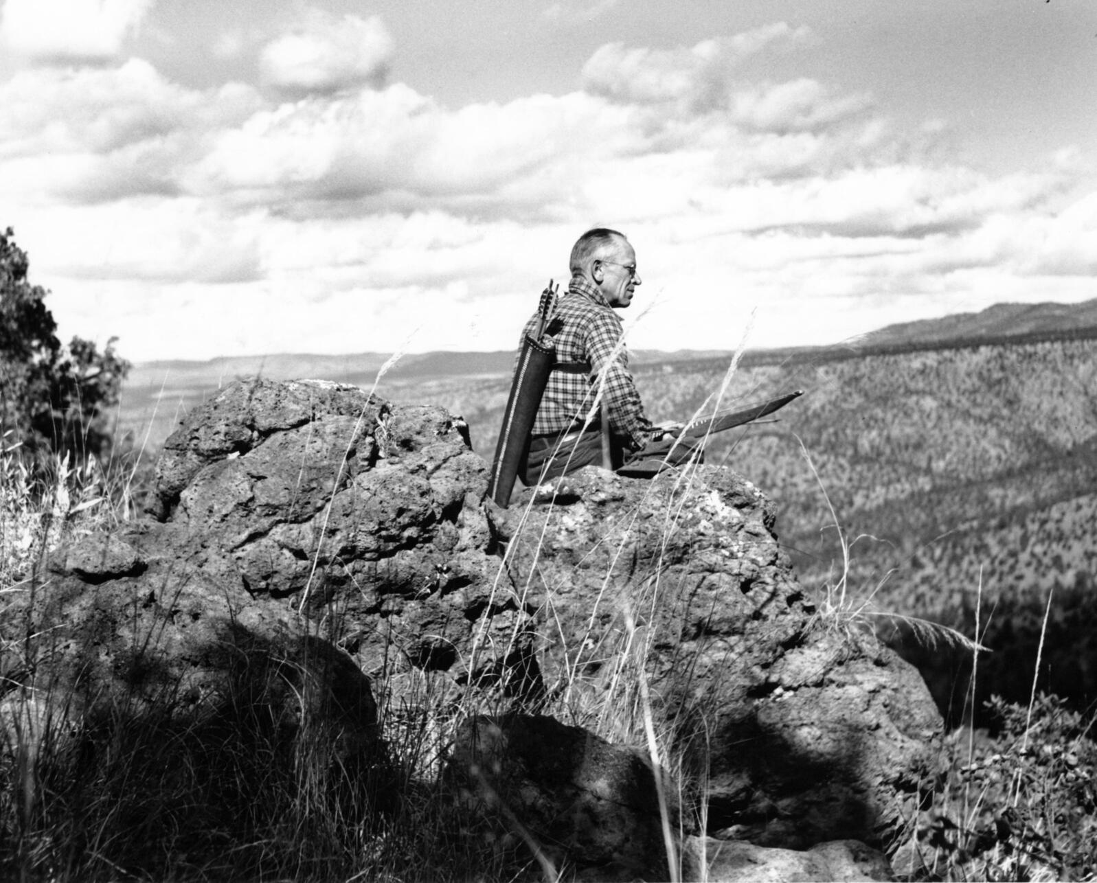 Aldo Leopold sitting on rimrock with quiver and bow at Rio Gavilan in Mexico. Starker Leopold/Aldo Leopold Foundation
