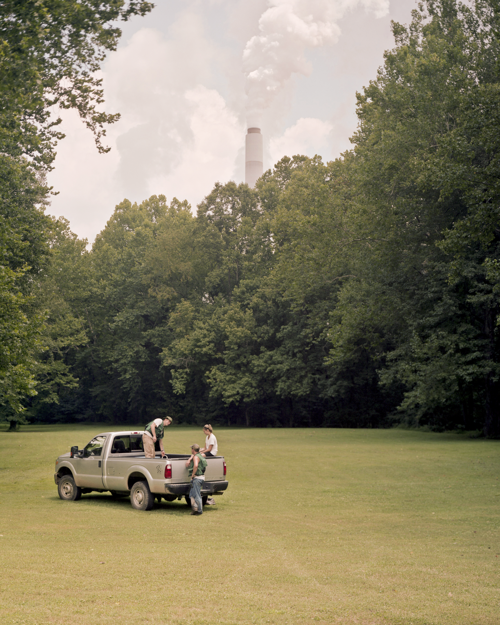 A 900-foot stack at West Virginia's E. Amos coal-fired power plant looms behind park staff. Photograph by Daniel Shea
