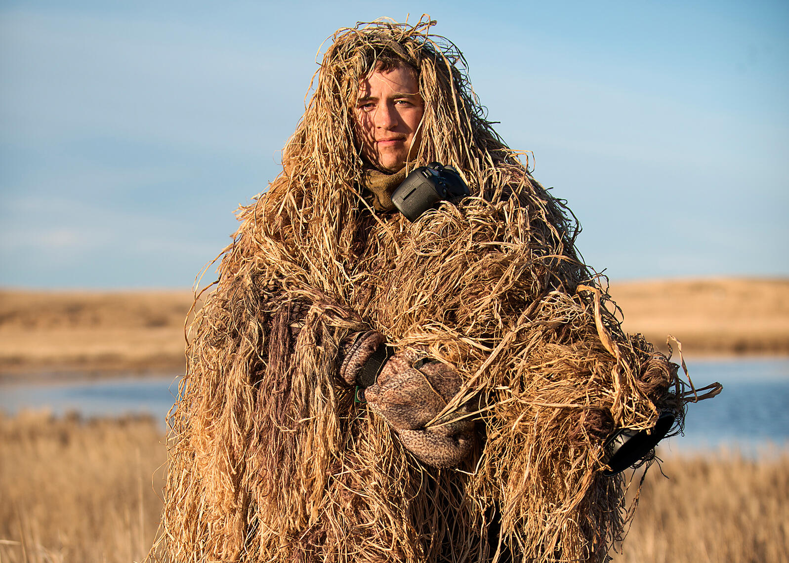 Adam Grimm in a ghillie suit that he uses for camouflage as he photographs the wild ducks in Eureka, South Dakota. Wild ducks are extremely wary of humans and will not come anywhere near a human who they can see. Jon Lowenstein