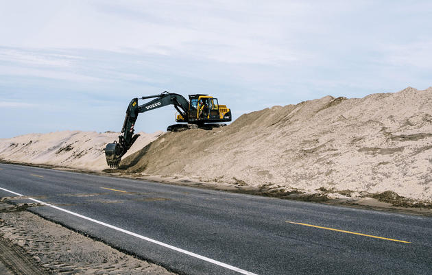 Crews work to repair man-made sand dunes on along NC 12 on Pea Island in the Outer Banks, NC. Greg Kahn.