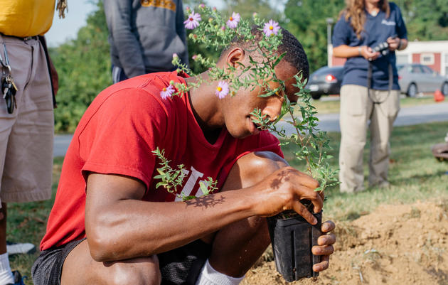 Glen Mills School student Jeremiah Williams helps out with the planting of a rain garden to provide insects for the school's Purple Martin colony. Cole Wilson