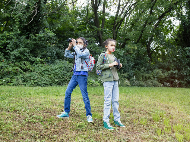 Two children, both wearing backpacks, masks, and holding binoculars, stand on the grass, trees behind them.