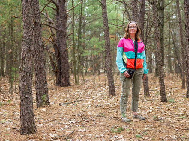 Professor Trish O'Kane, a woman wearing glasses and a pink and green jacket, stands in a wooded grove in Burlington, Vermont, where she taught an outdoor class during the COVID-19 pandemic.