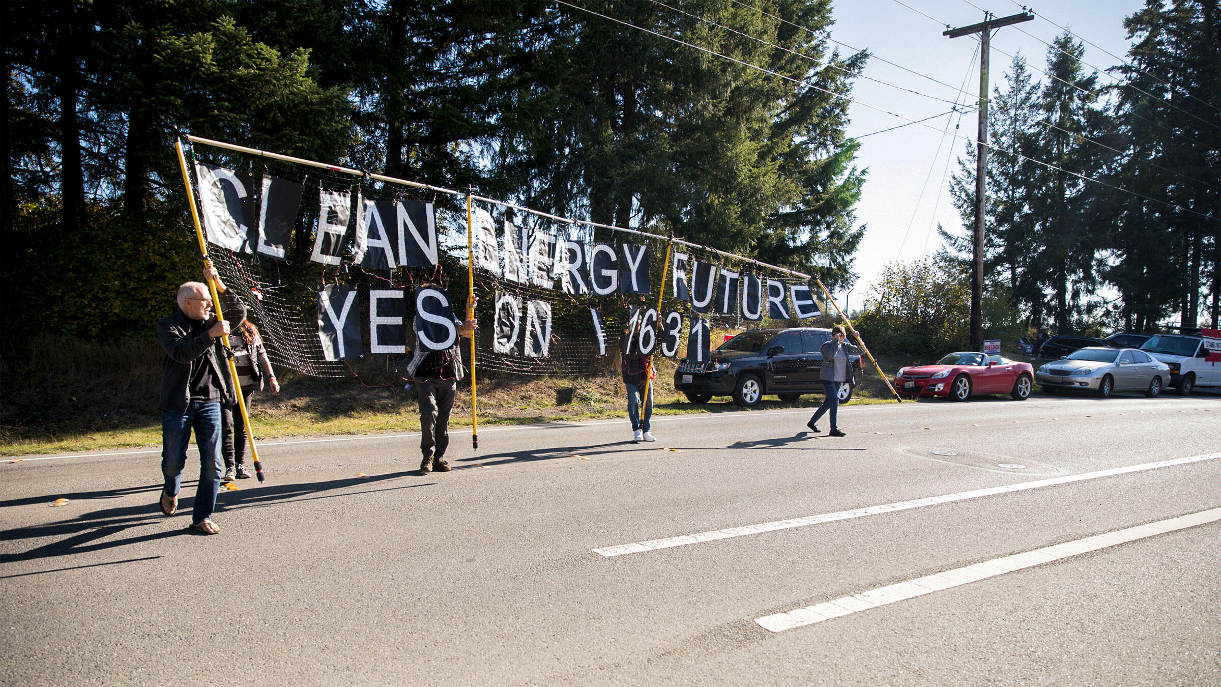 Campaign signage seen walking across the street in front of Western States Petroleum Association building during I-1631 rally in Lacey, Washington, Oct. 17, 2018. Matt M. McKnight/Cascade Public Media 2018