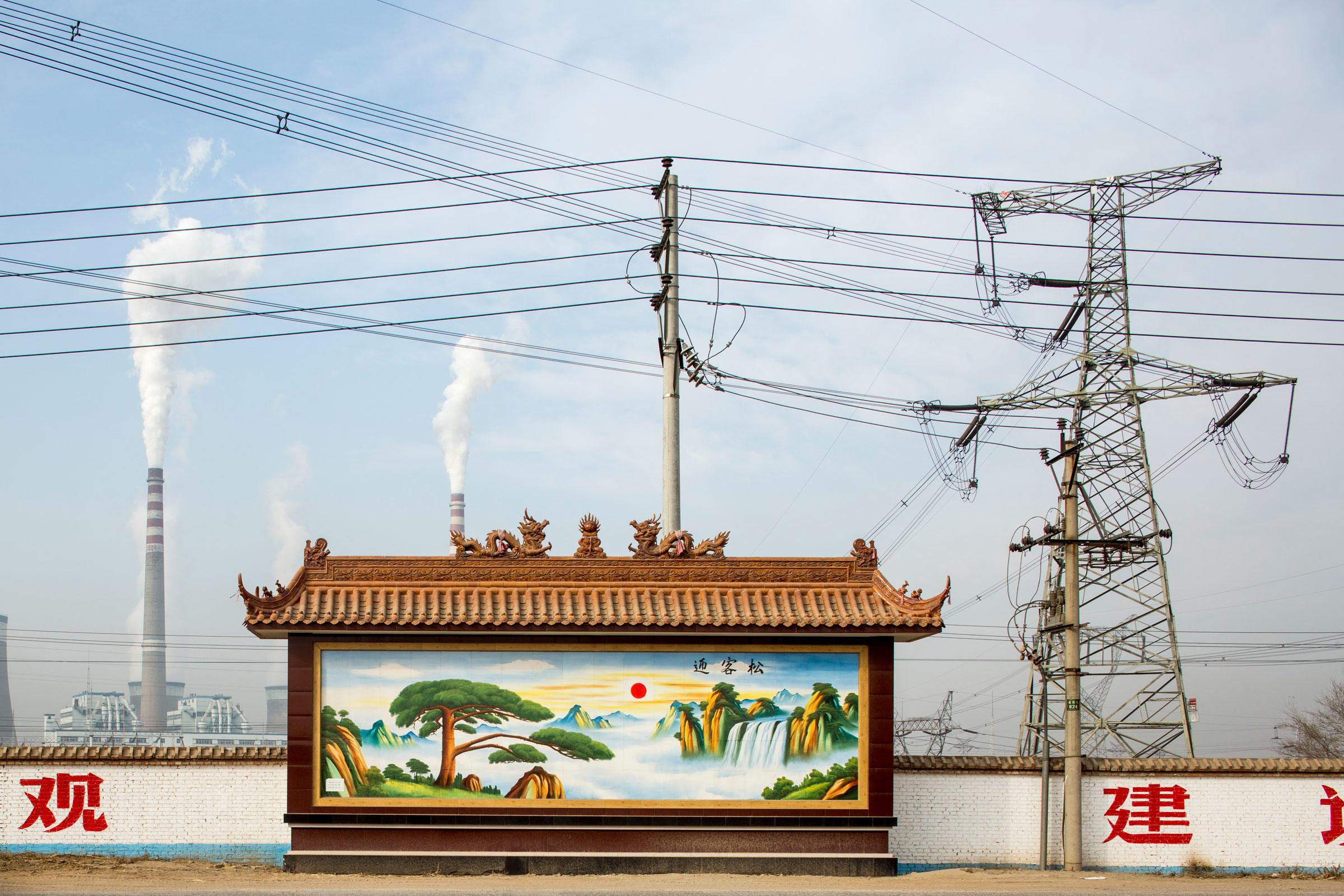 A painting of an idyllic Chinese landscape stands in front of smokestacks at Datong No. 2 Power Station in Shanxi Province, China. Paul Souders/Corbis