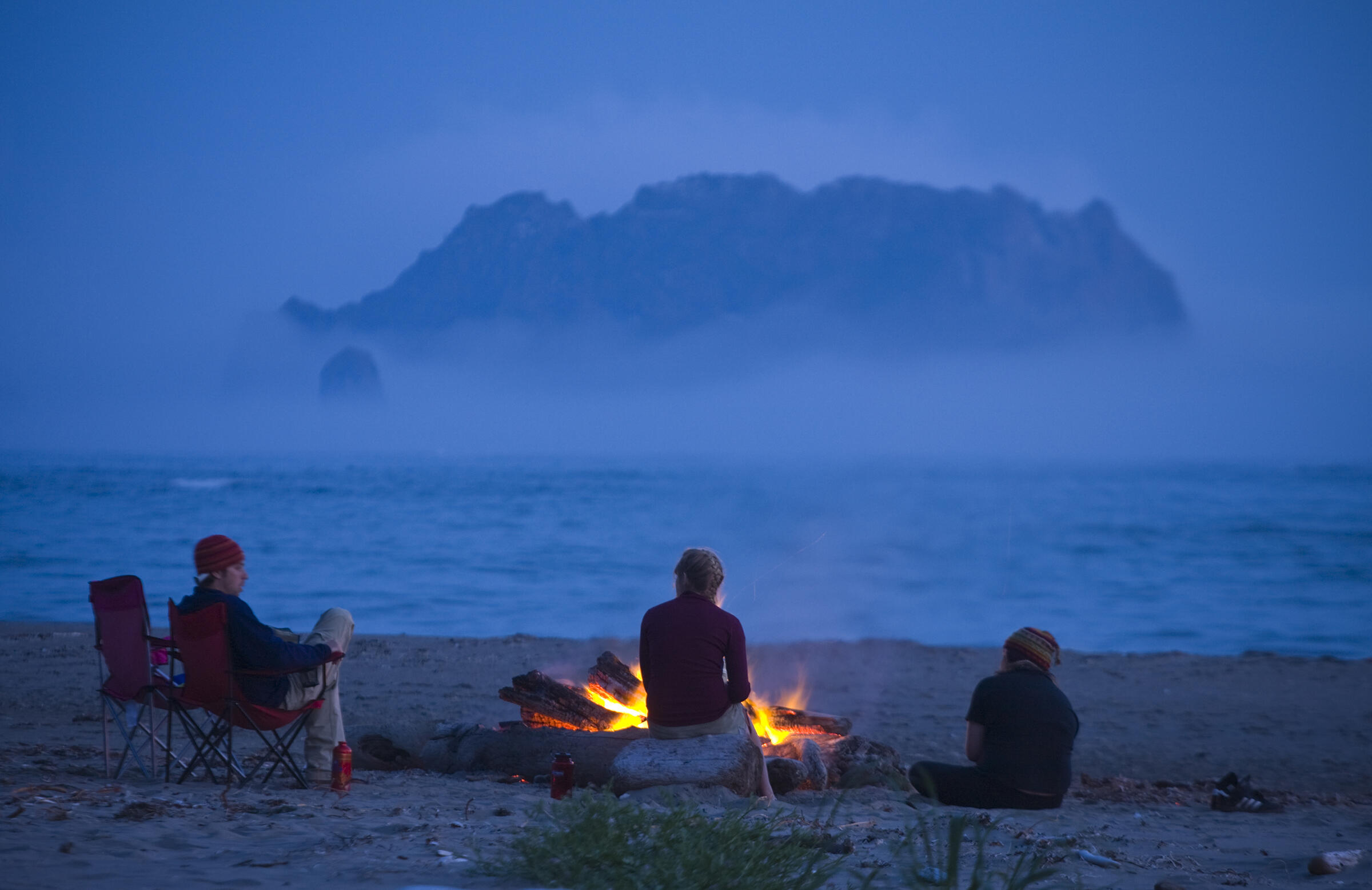 Campers sit by a campfire on the beach at Norwegian Memorial, Olympic National Park North Coast, Washington. Ethan Welty/Tandemstock.com