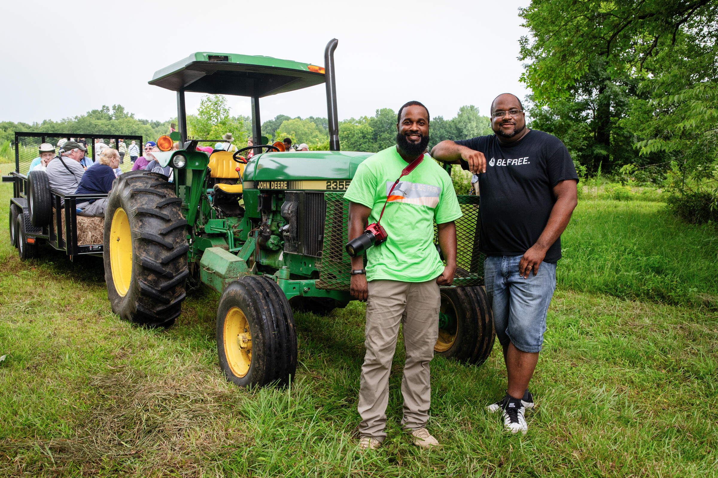 Two men—the one on the left in a green shirt and the other in a black shirt—smile at the camera and stand in front of a green tractor. Behind the tractor is a wagon filled with birders. More birders walk in the green field behind the wagon.