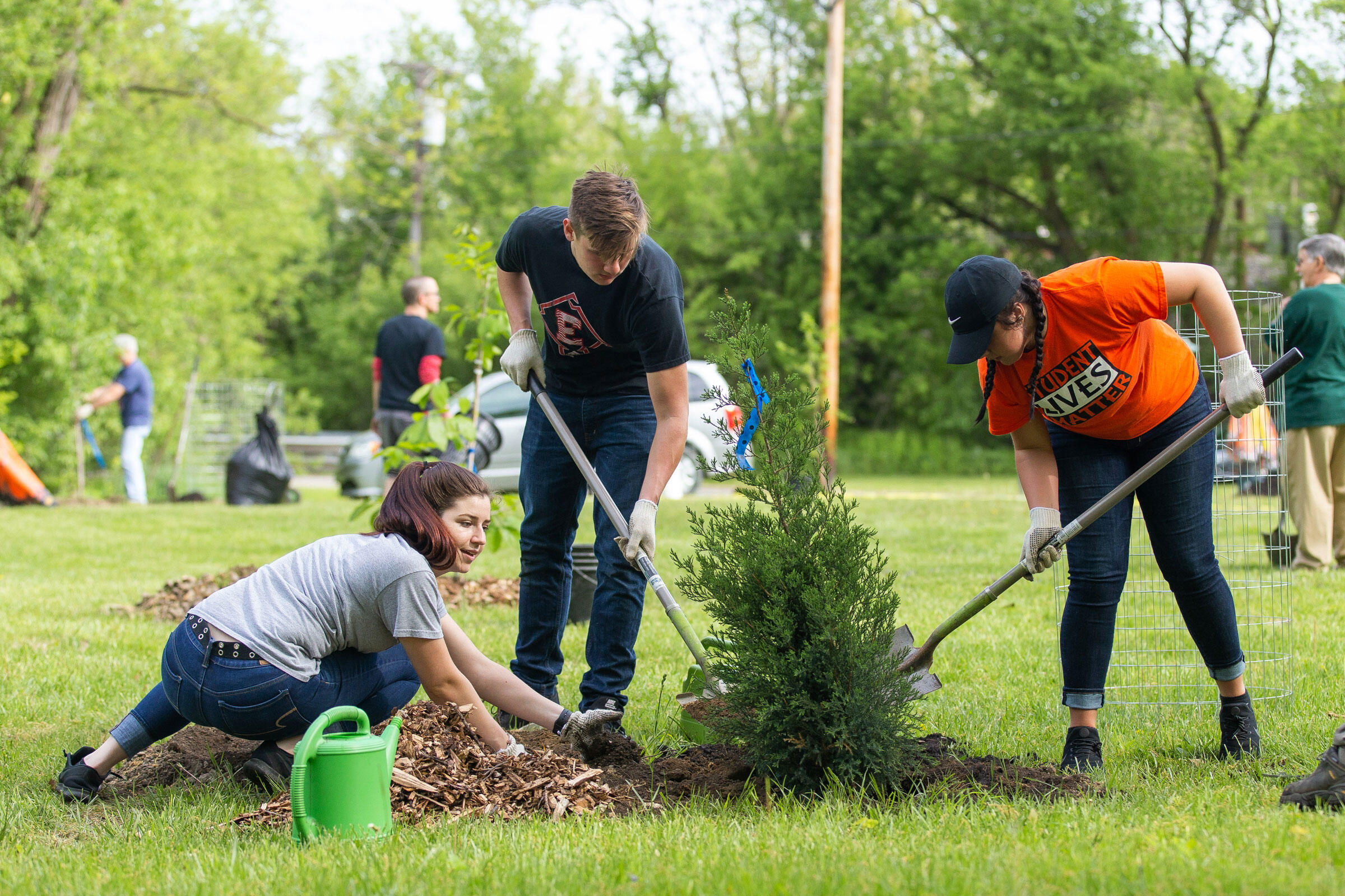 High school volunteers Paige Keim, Gage Norris, and Zoe Gonzalez plant an eastern red cedar tree at the Black River Audubon Park in Elyria, Ohio. Allison Farrand