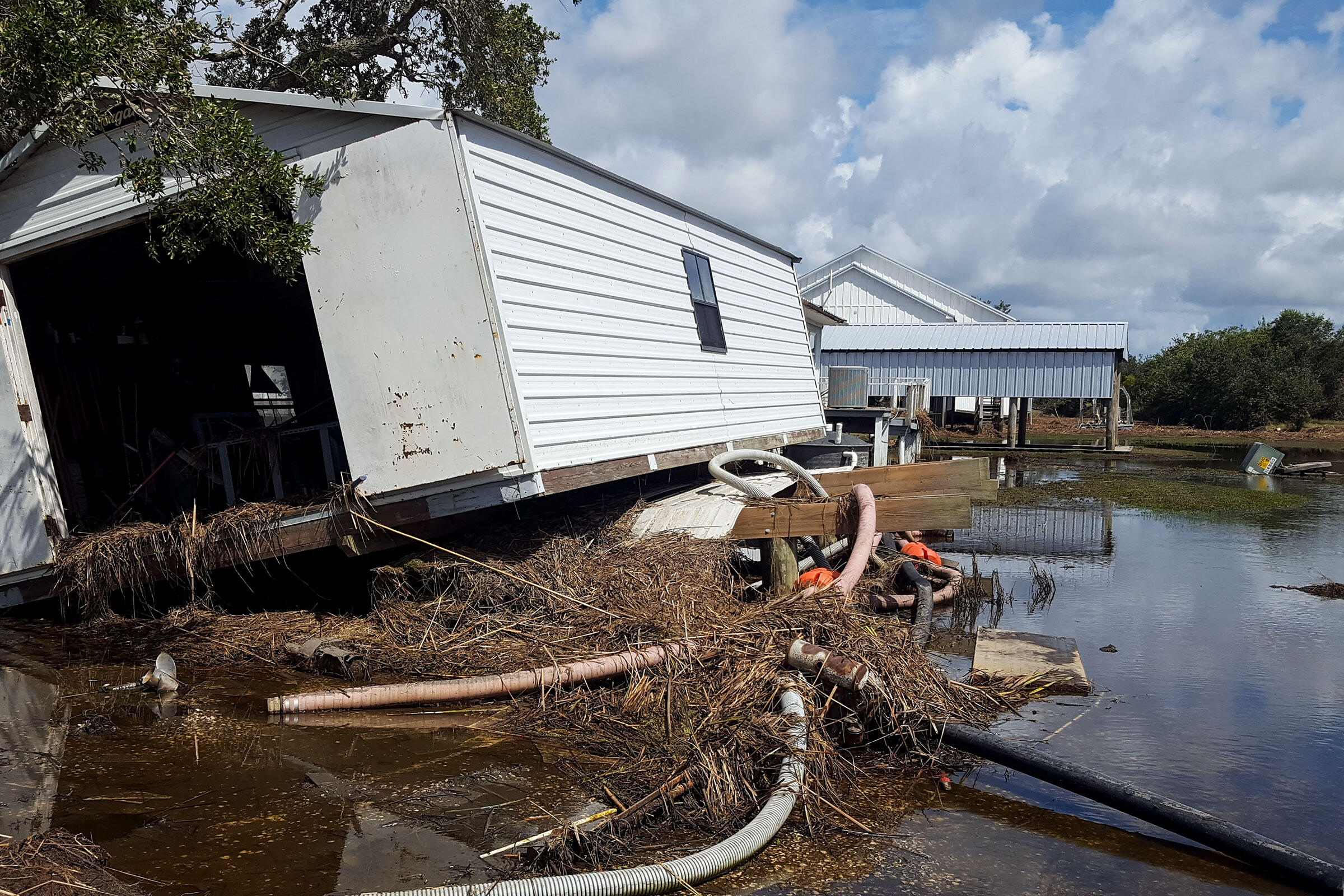 A storage shed was knocked off its foundation by storm surge and filled with debris at Rainey Wildlife Sanctuary. Erik Johnson/Audubon