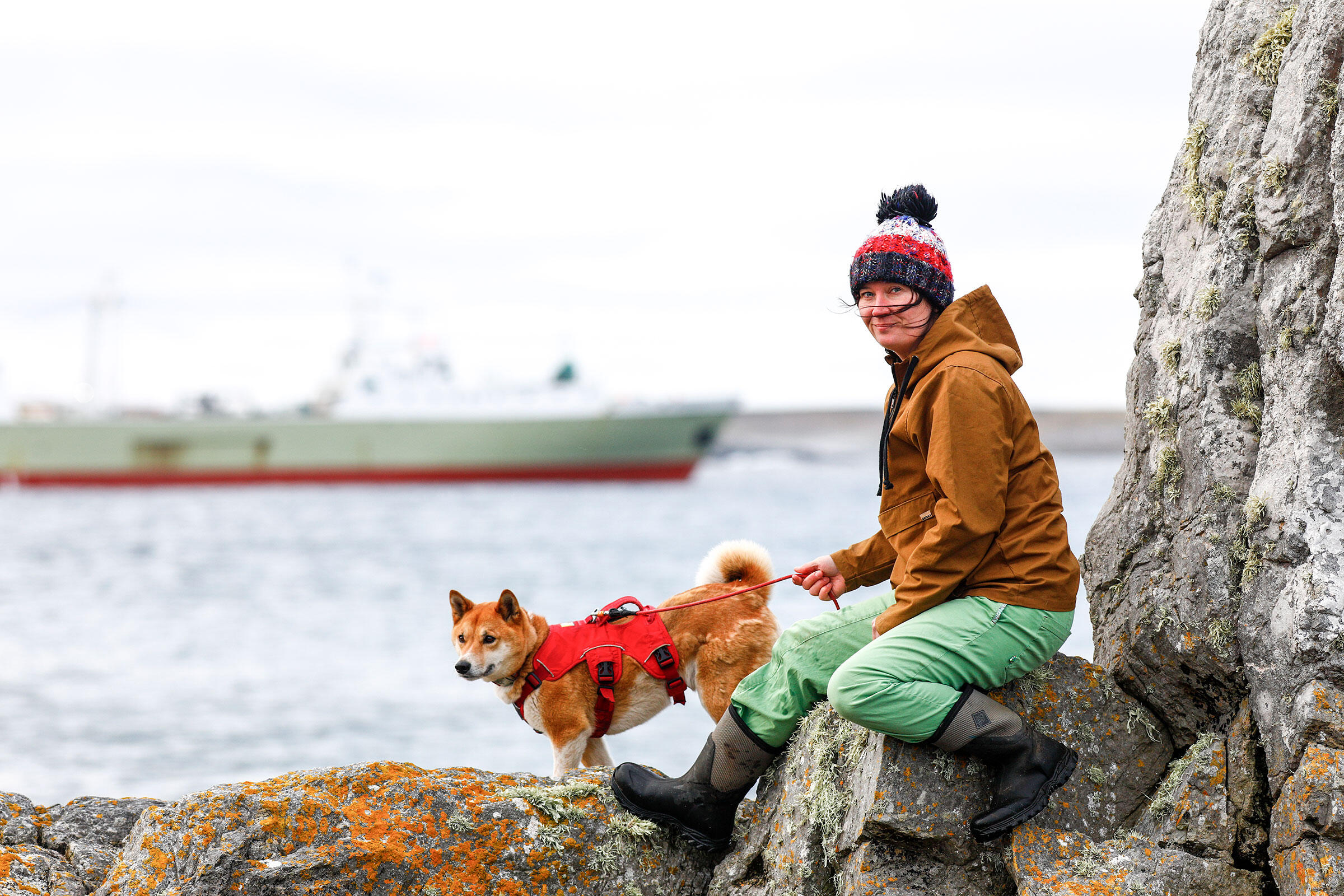 A woman in green pants, a brown coat, and red, brown, and white winter cap sits on a large rock with a sheer rock face to her right. She holds a leash attached to an orange and white dog standing on rocks mottled with orange lichens. A ship floats in the background.