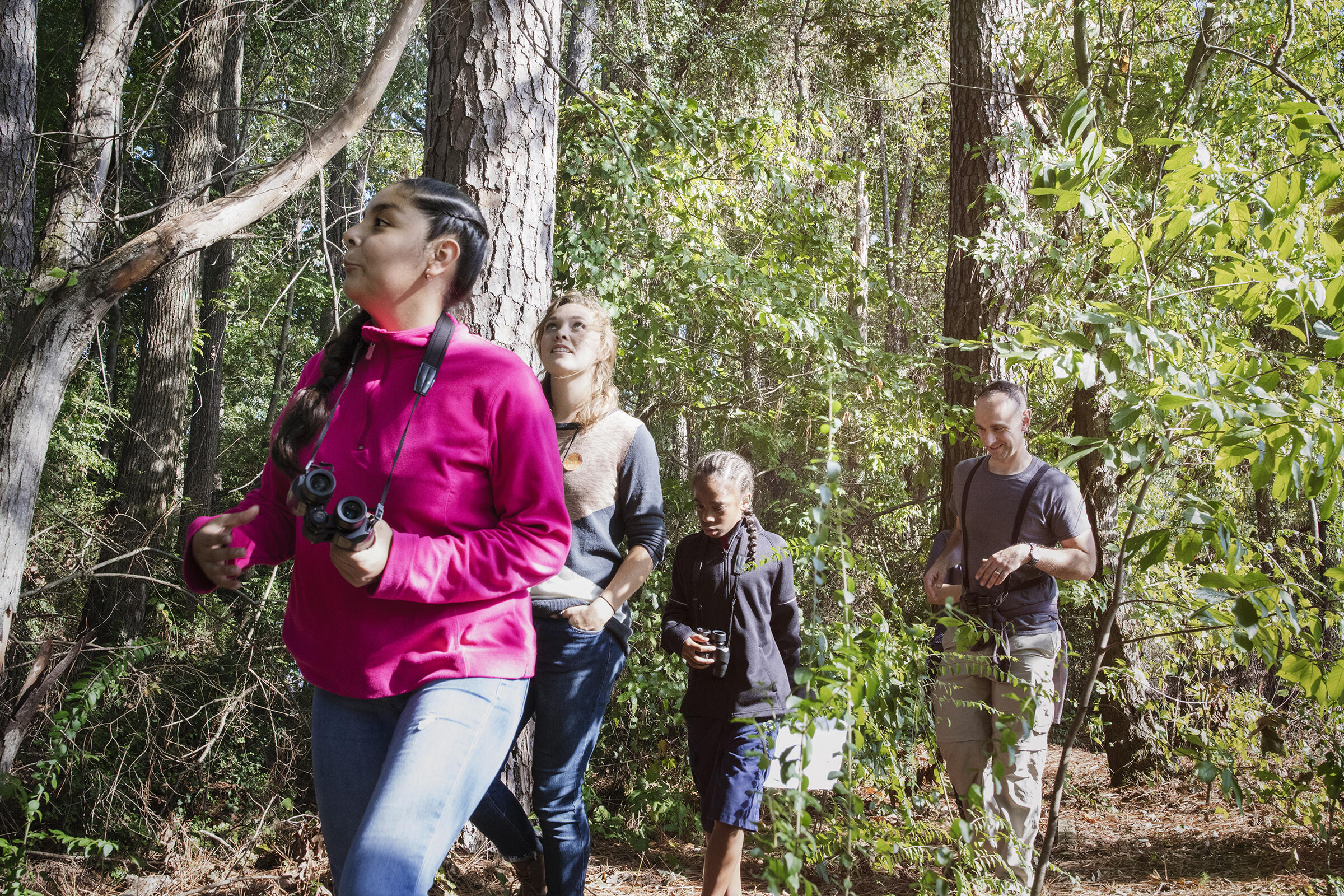 The class joins Baker and Birmingham Audubon's Ansel Payne to search for Brown-headed Nuthatches and Red-bellied Woodpeckers in their woods. Mike Fernandez/Audubon