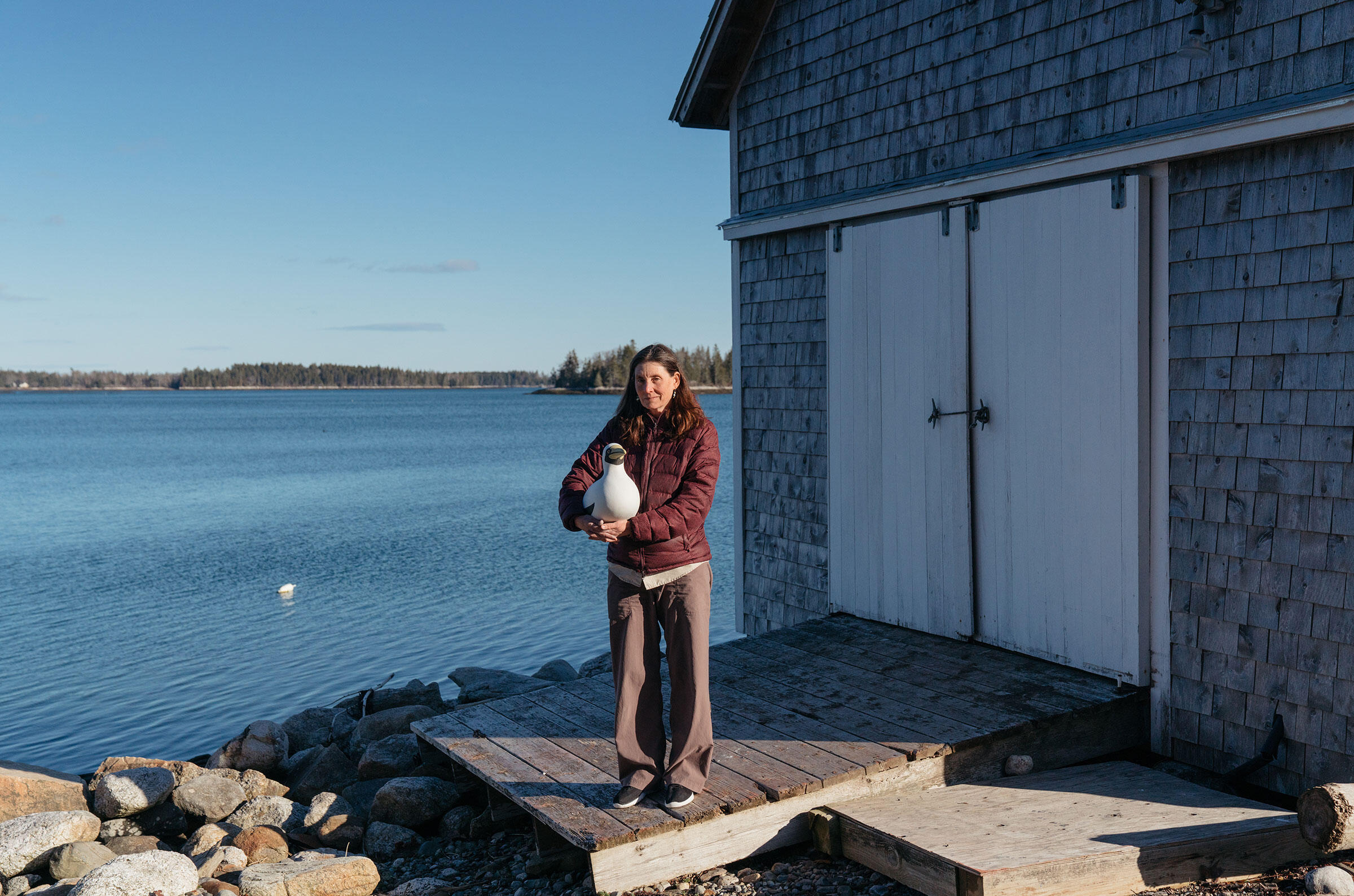 Sue Schubel, decoy project manager, with a handmade Australasian Gannet decoy at the dock to Hog Island Audubon Camp. Tristan Spinski