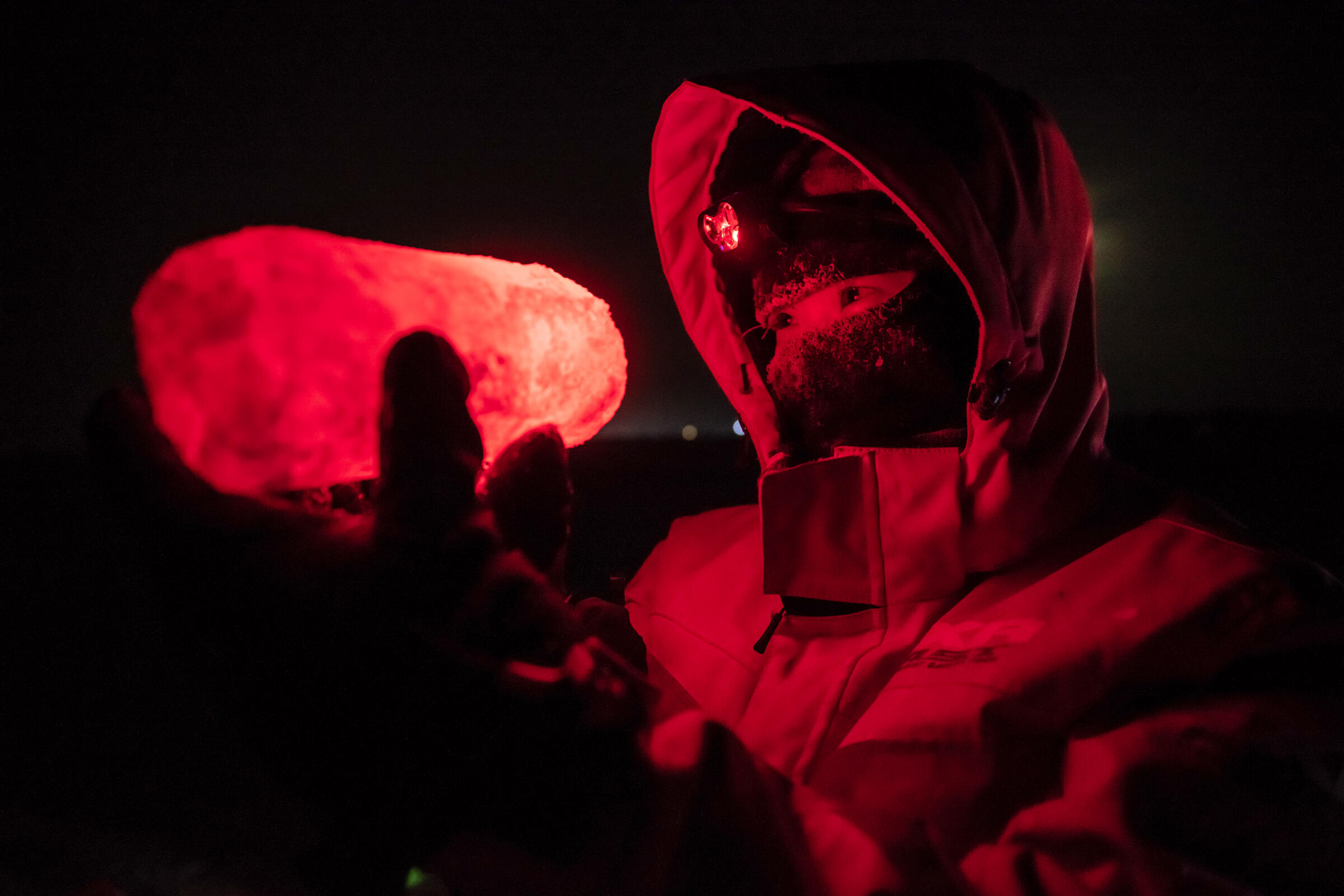 Allison Fong, an Alfred Wegener Institute biologist, inspects part of an ice core under red light. The red light is necessary so the scientists do not artificially stimulate microbes living in the ice. Esther Horvath