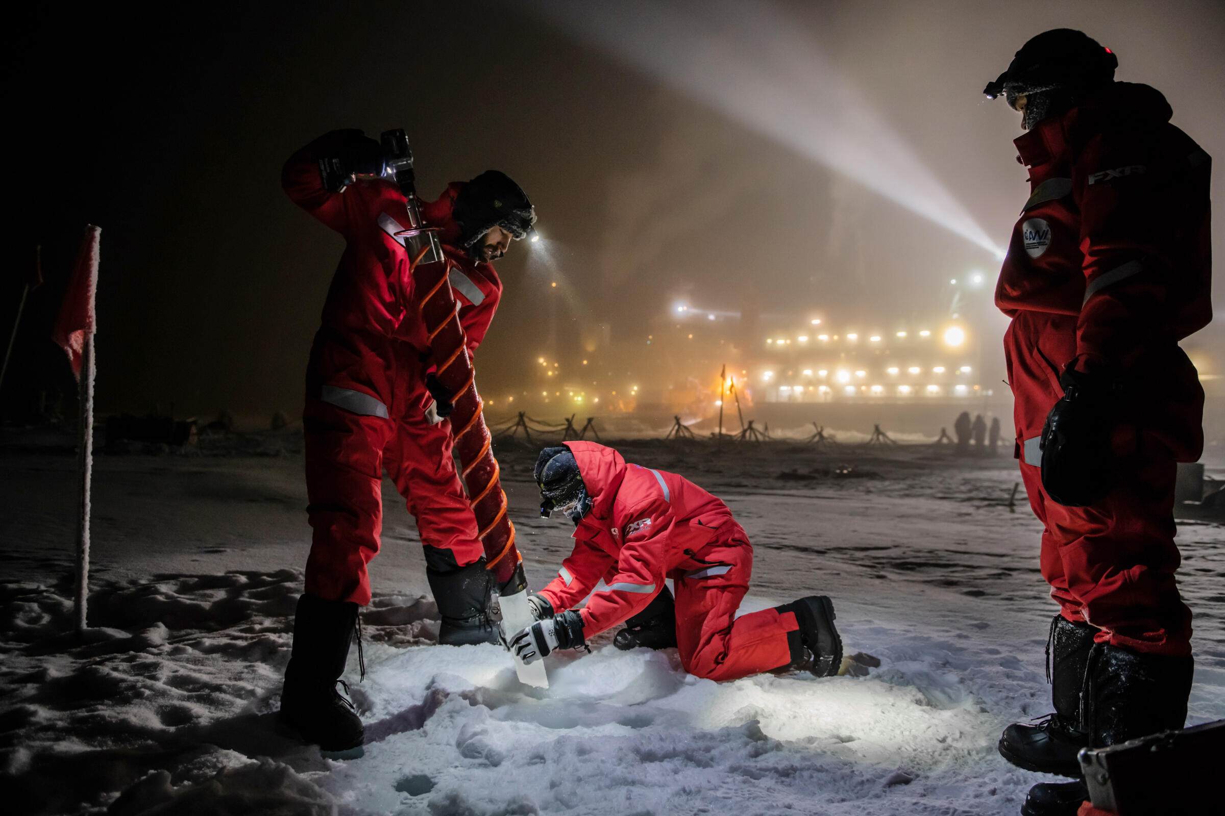 Three members of the ice team collect a test core. A scientist kneeling on the ground removes a cylindrical piece of ice from a drill approximately five feet long. Esther Horvath
