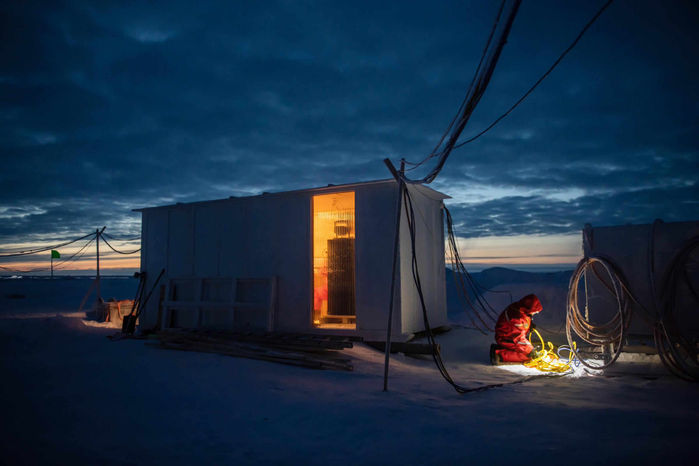 Warm, orange light shines through the doorway of the Met City tech hut—a container to keep computers warm, and large enough to house scientists huddling for warmth, too. A scientist kneels beside the hut untangling yellow cables. Esther Horvath