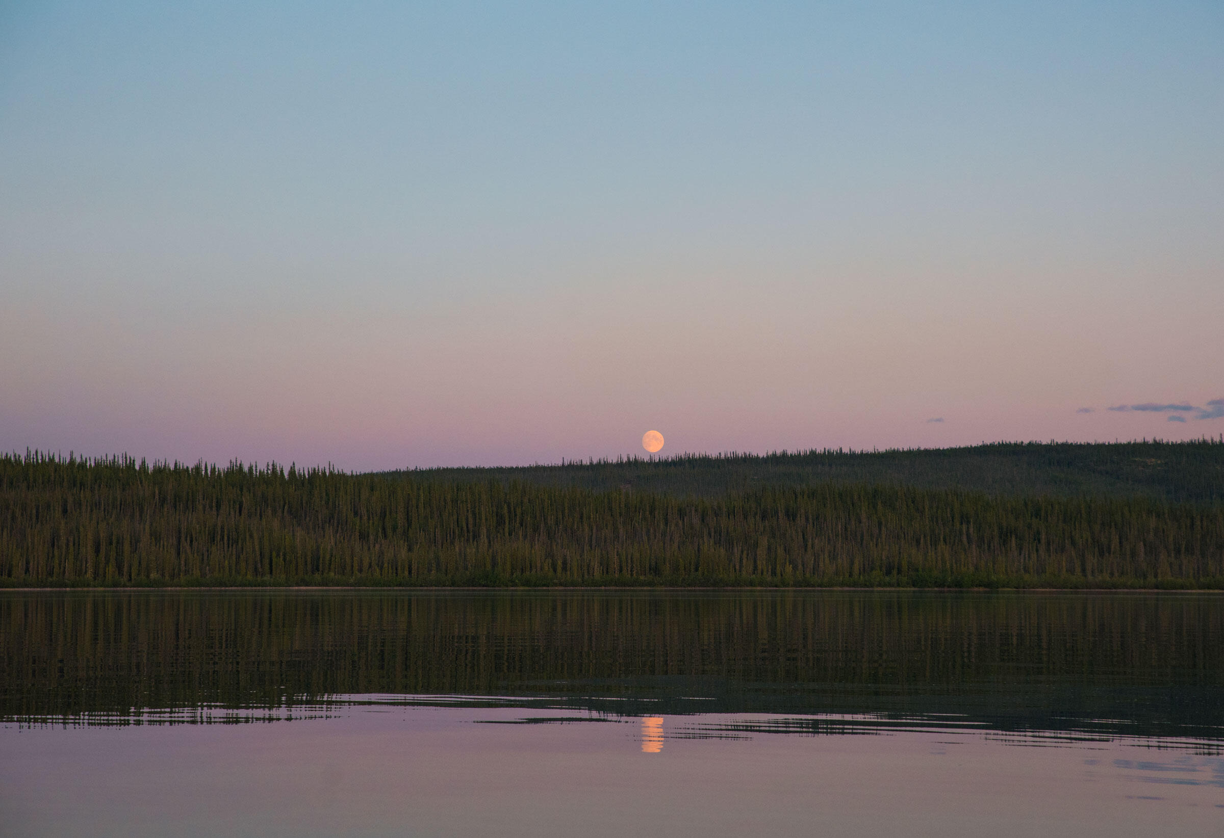 A near full-moon is lit by the Northern midnight sun as it touches the horizon at 11 p.m. Pat Kane