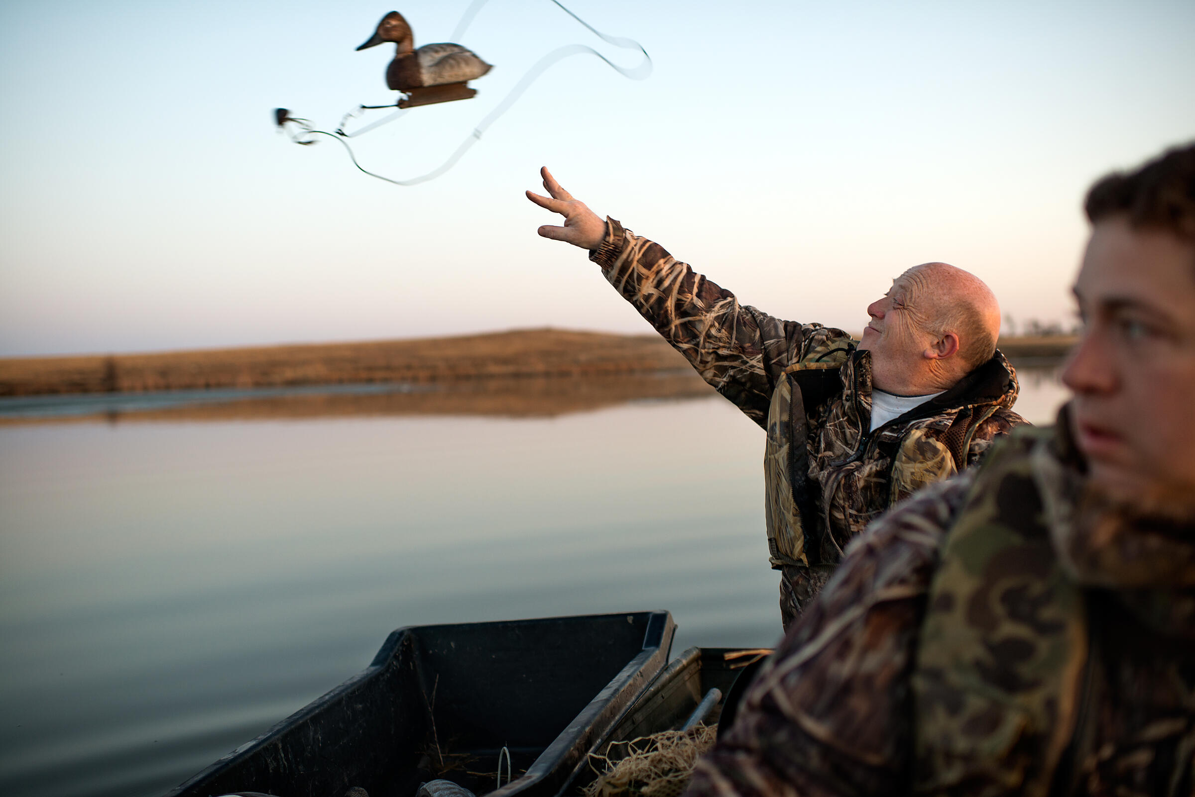 Tim Taylor, bird artist and Adam Grimm's best friend, flings a decoy into a pond at South Dakota's Job Waterfowl Production Area, while Grimm rows the boat. Jon Lowenstein