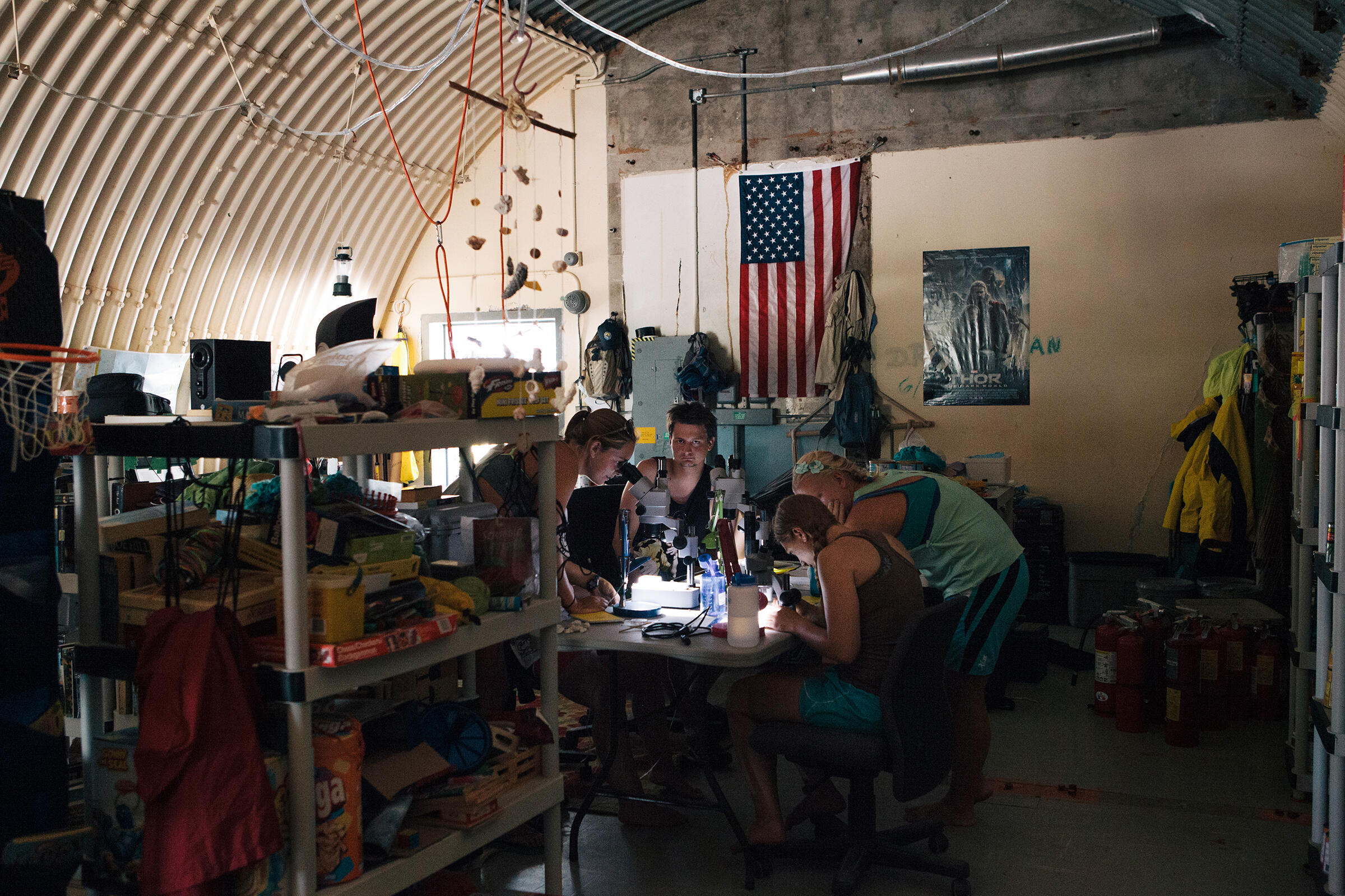 """Strike team members identify various ant species in the """"Ant Cave,"""" a repurposed bunker that now serves as a library, laboratory, kitchen, and pantry. Tristan Spinski"""