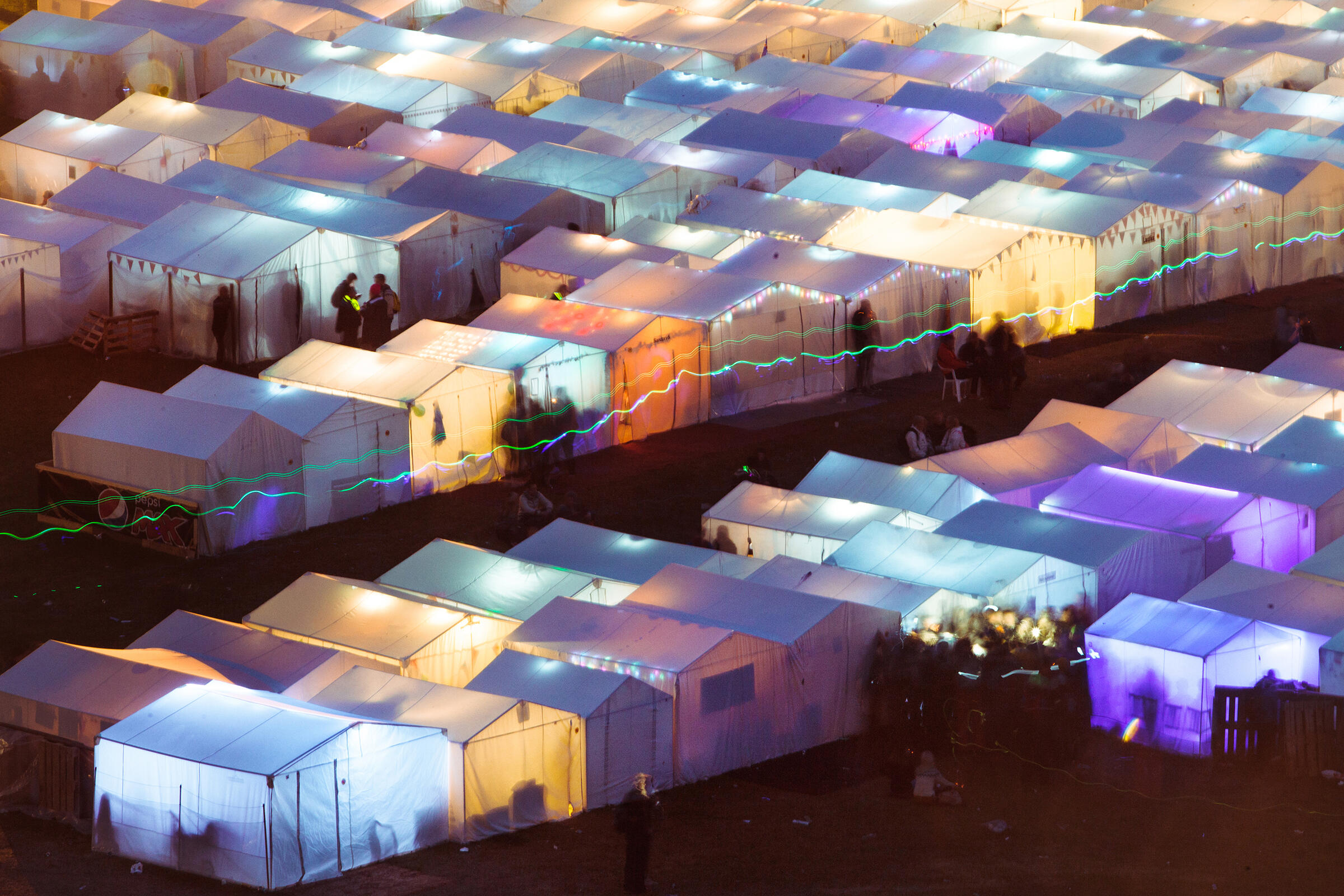 Locals and their families and friends have a long tradition of setting up a makeshift village of white tents that serve as social hubs for drinking, eating, and singing—day and night. Tristan Spinski