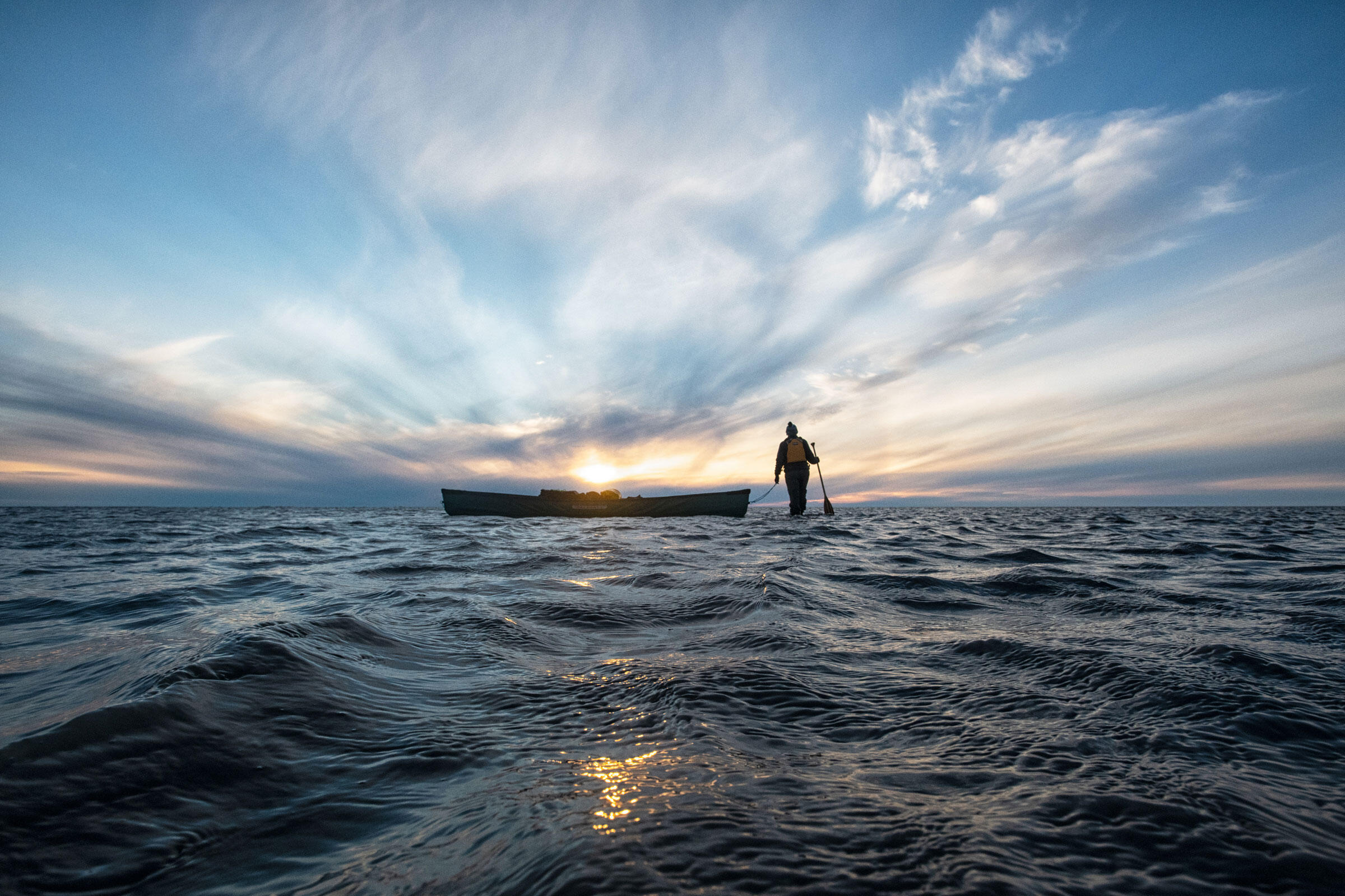 Morrison walks a canoe through the shallow waters of the Hula Hula river delta. Peter Mather