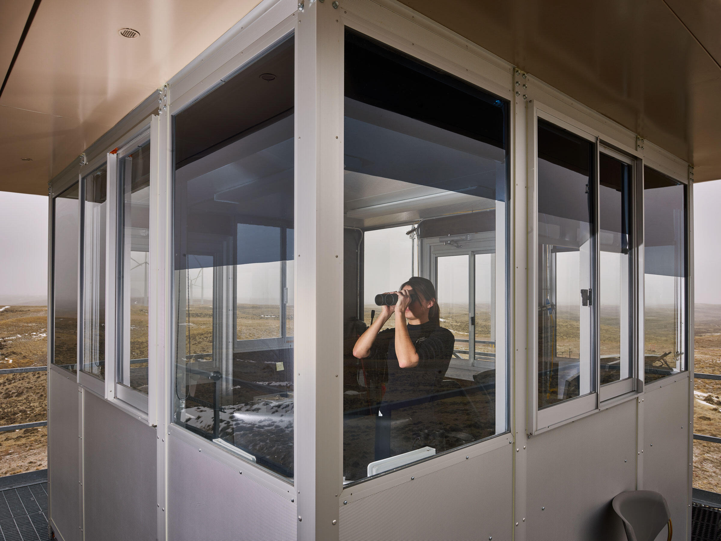Inside an observation tower, Taylor Berge, an eagle observation specialist, looks for birds at Top of the World. Spencer Lowell