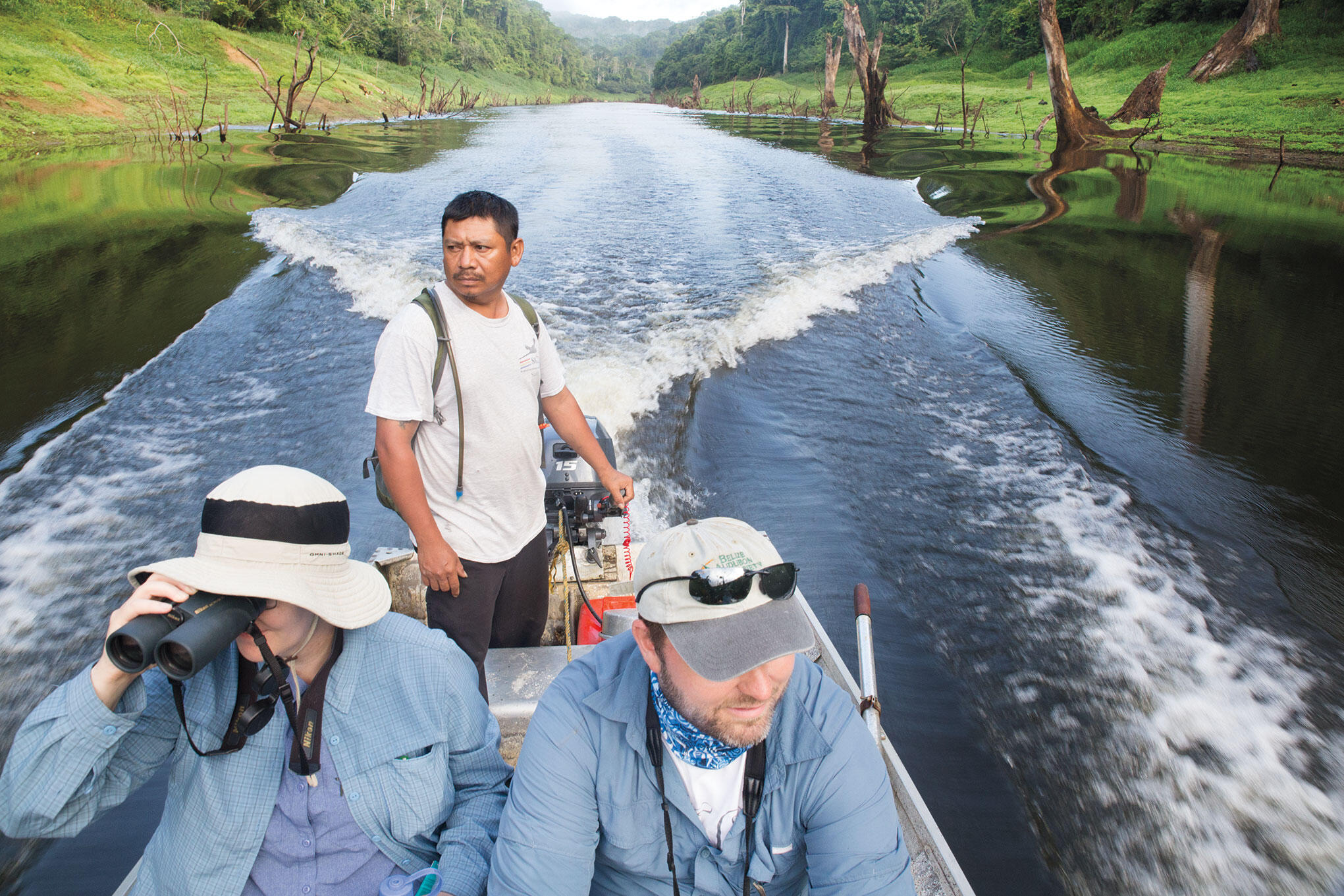 Luis Mai (standing), the longest-tenured ranger for Scarlet Six, navigates upstream in the Macal River. Camilla Cerea/Audubon