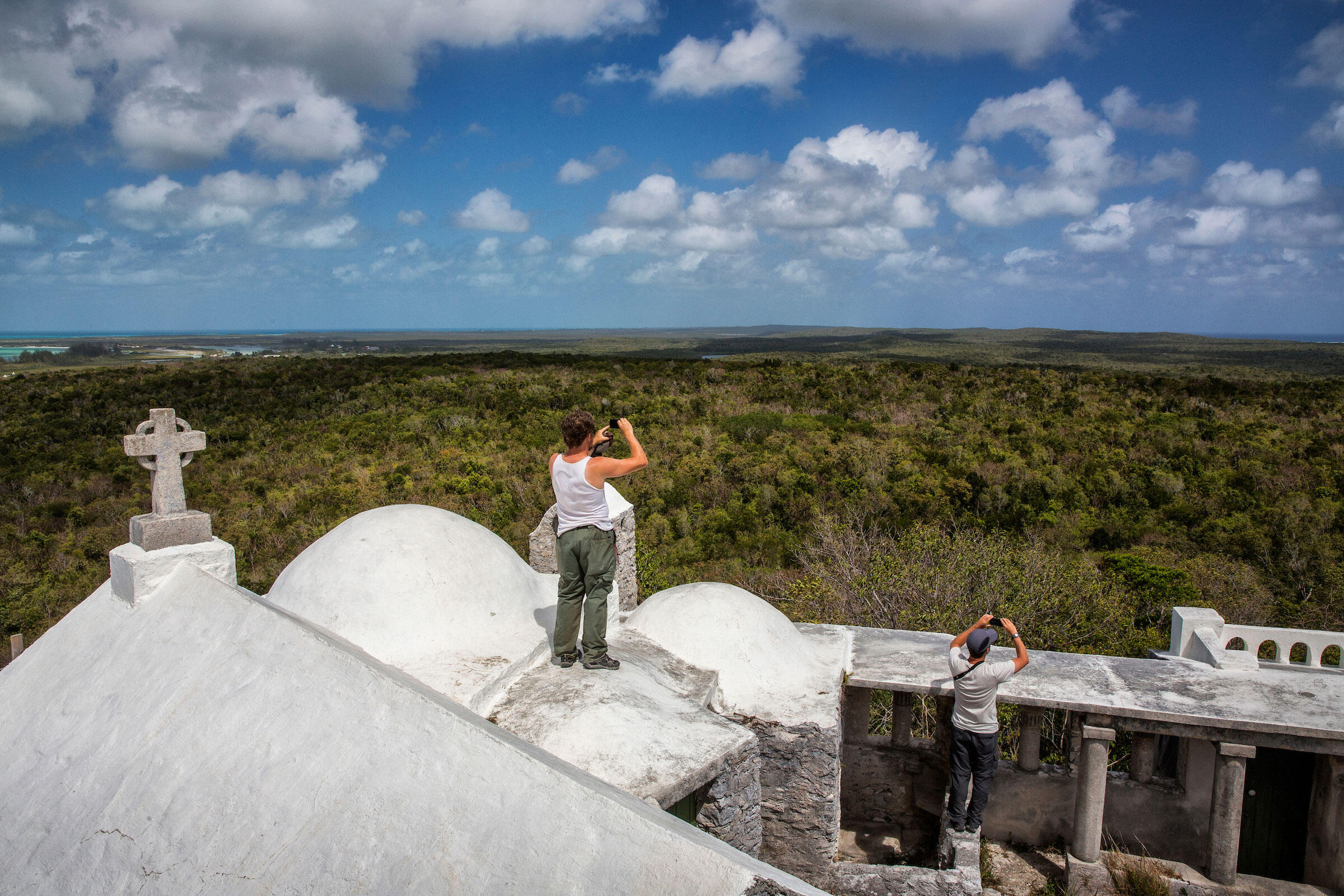 Cooper and Chris Fox take a break from evaluating Kirtland's wintering habitat to check out Mount Alvernia on Como Hill—the highest point in the Bahamas. Karine Aigner