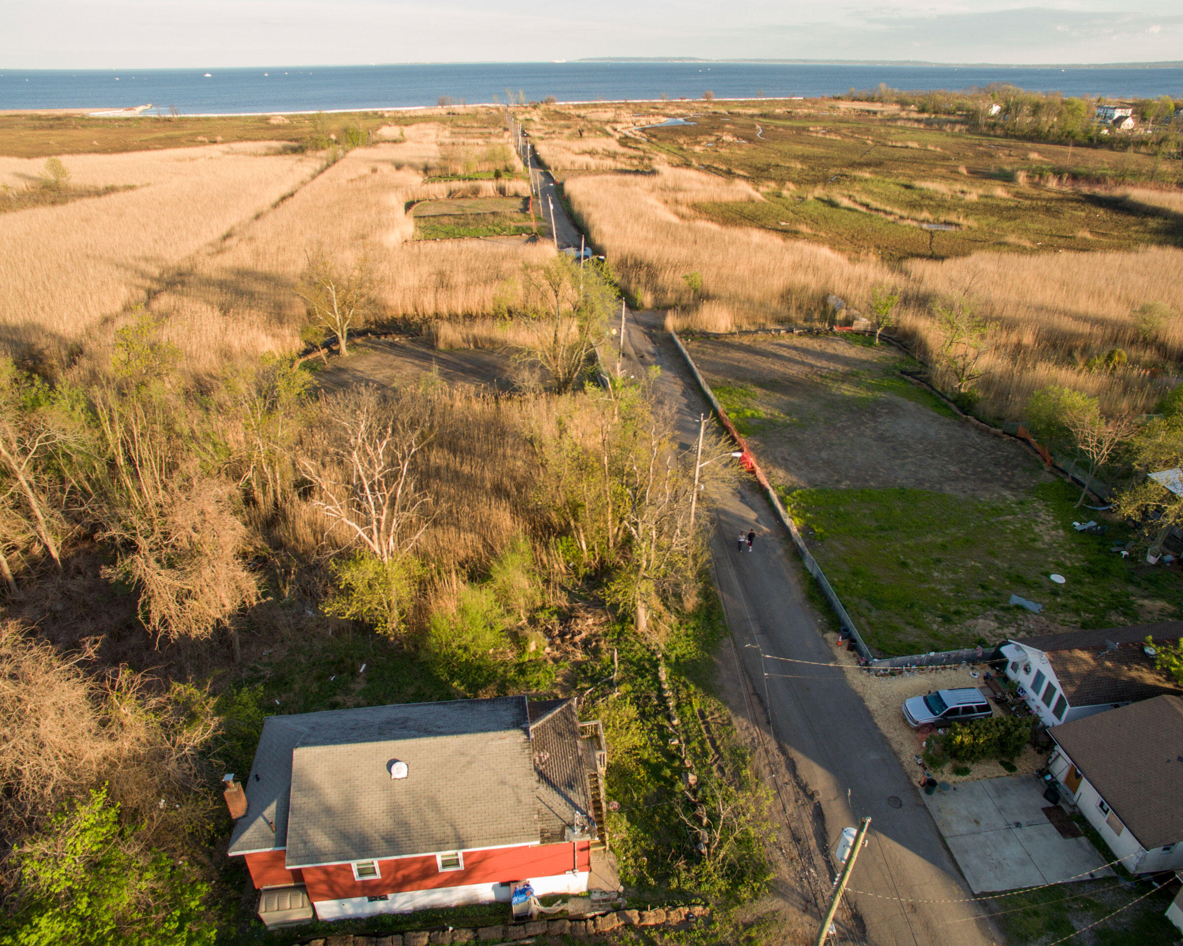 Oakwood Beach's Kissam Avenue was once a quiet street lined with bungalows and beach houses. Today, Kissam Avenue remains a quiet street, but it's now lined with marshland and regrowing lots. April 23, 2016. Hillary Eggers